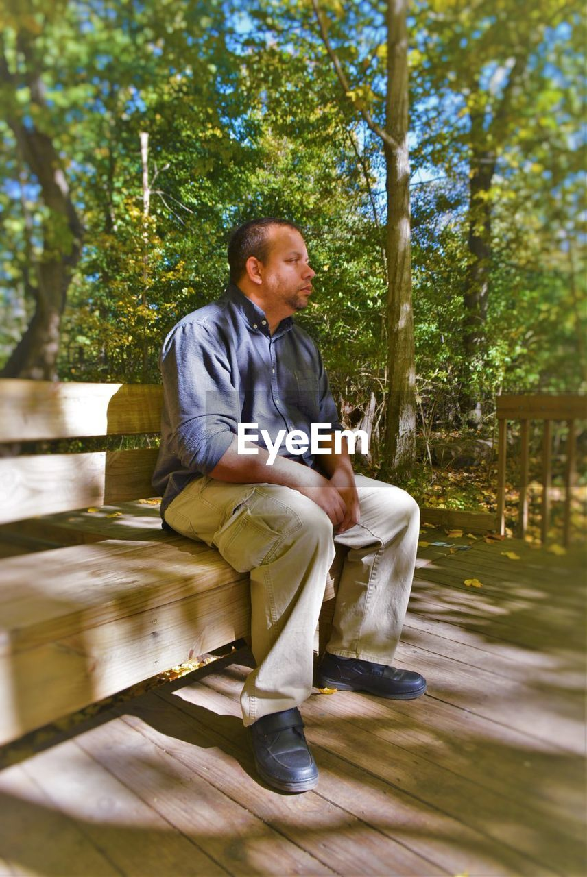 Full length of tensed man sitting on bench at park
