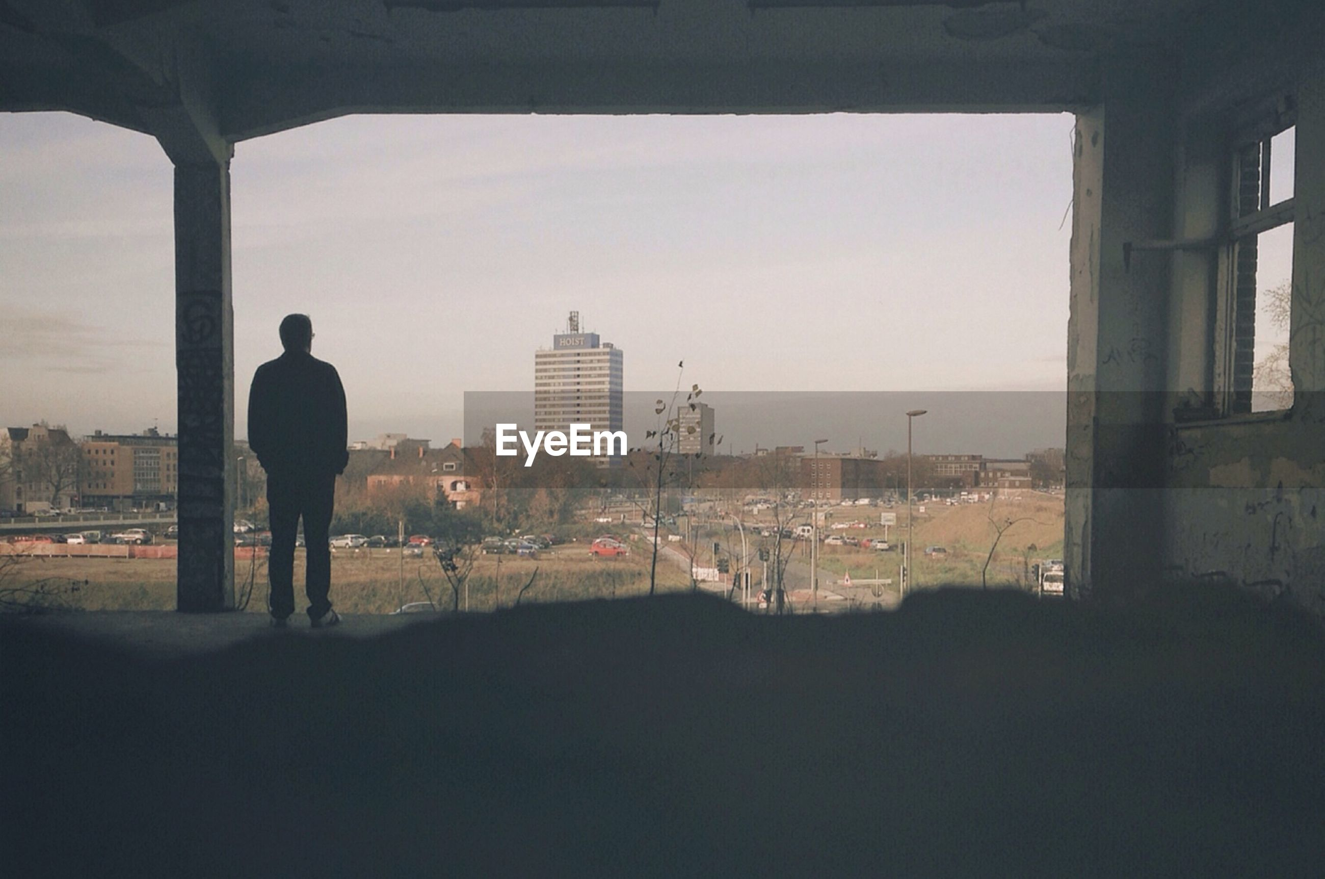 Rear view of man looking at city while standing at porch