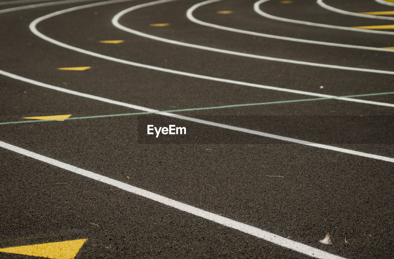 sport, curve, track and field, competition, running track, no people, sports race, outdoors, sports track, day, absence, empty, competitive sport, backgrounds, high angle view, stadium, in a row, selective focus, full frame, challenge, surface level