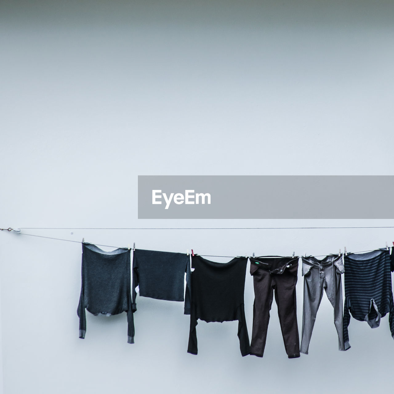 hanging, clothing, drying, clothesline, no people, copy space, laundry, in a row, side by side, group of objects, white color, day, rope, clothespin, textile, nature, sky, choice, coathanger, variation