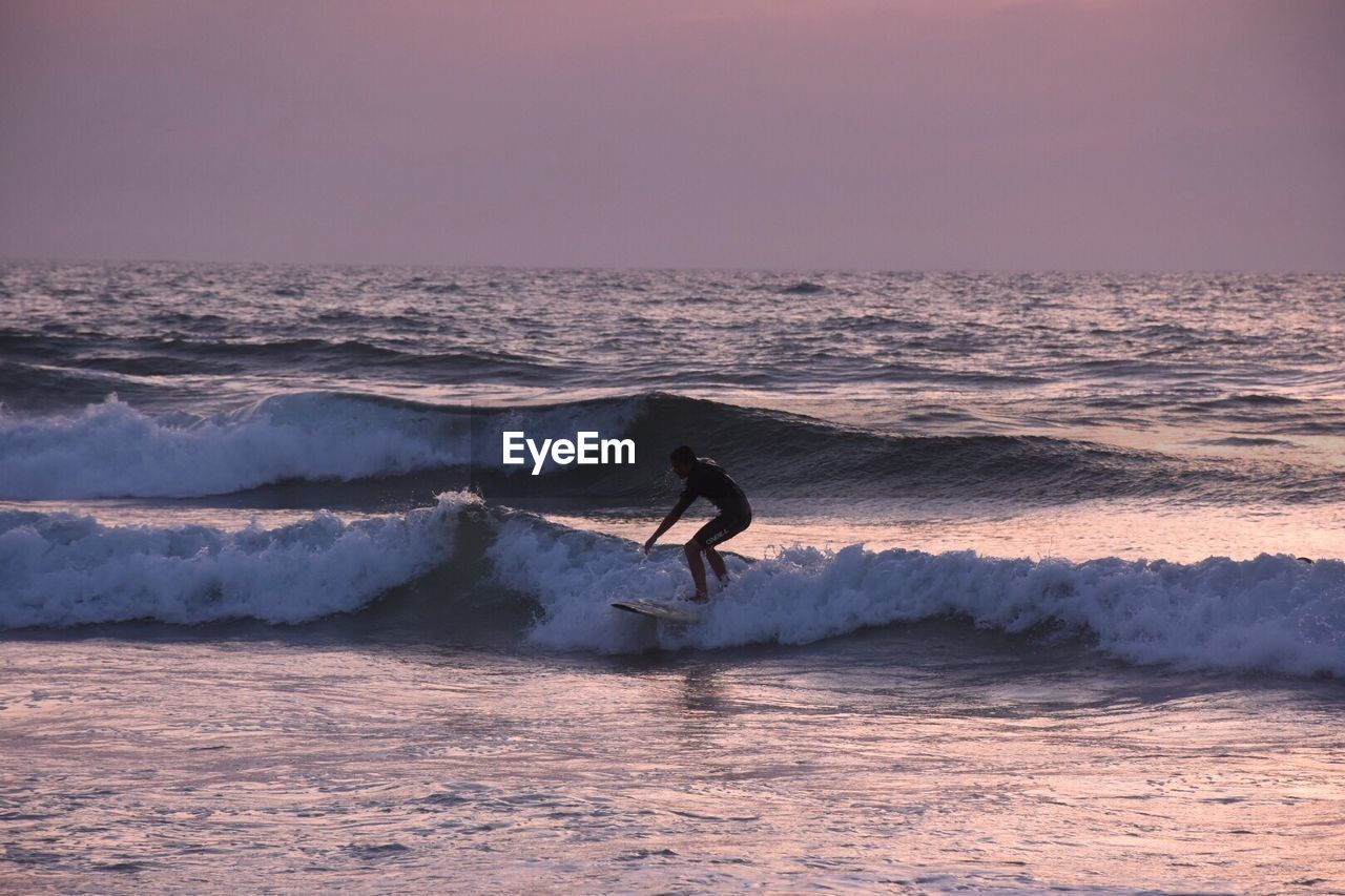 Man Surfing On Wave In Sea Against Sky At Dusk