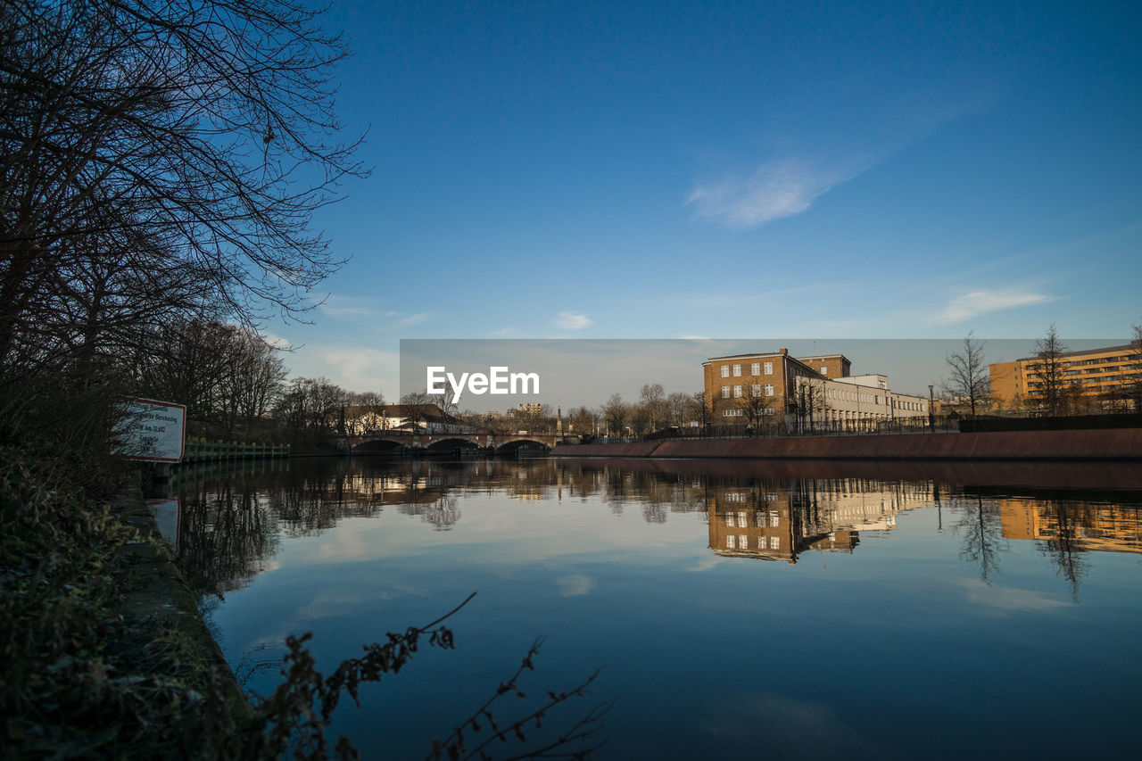 reflection, architecture, water, built structure, building exterior, sky, no people, waterfront, tree, standing water, river, outdoors, nature, city, bare tree, day