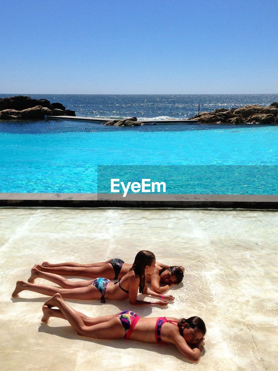 bikini, sea, water, two people, beach, day, young adult, full length, outdoors, summer, nature, clear sky, beauty in nature, scenics, vacations, young women, blue, sand, togetherness, shirtless, relaxation, lying down, real people, horizon over water, sky