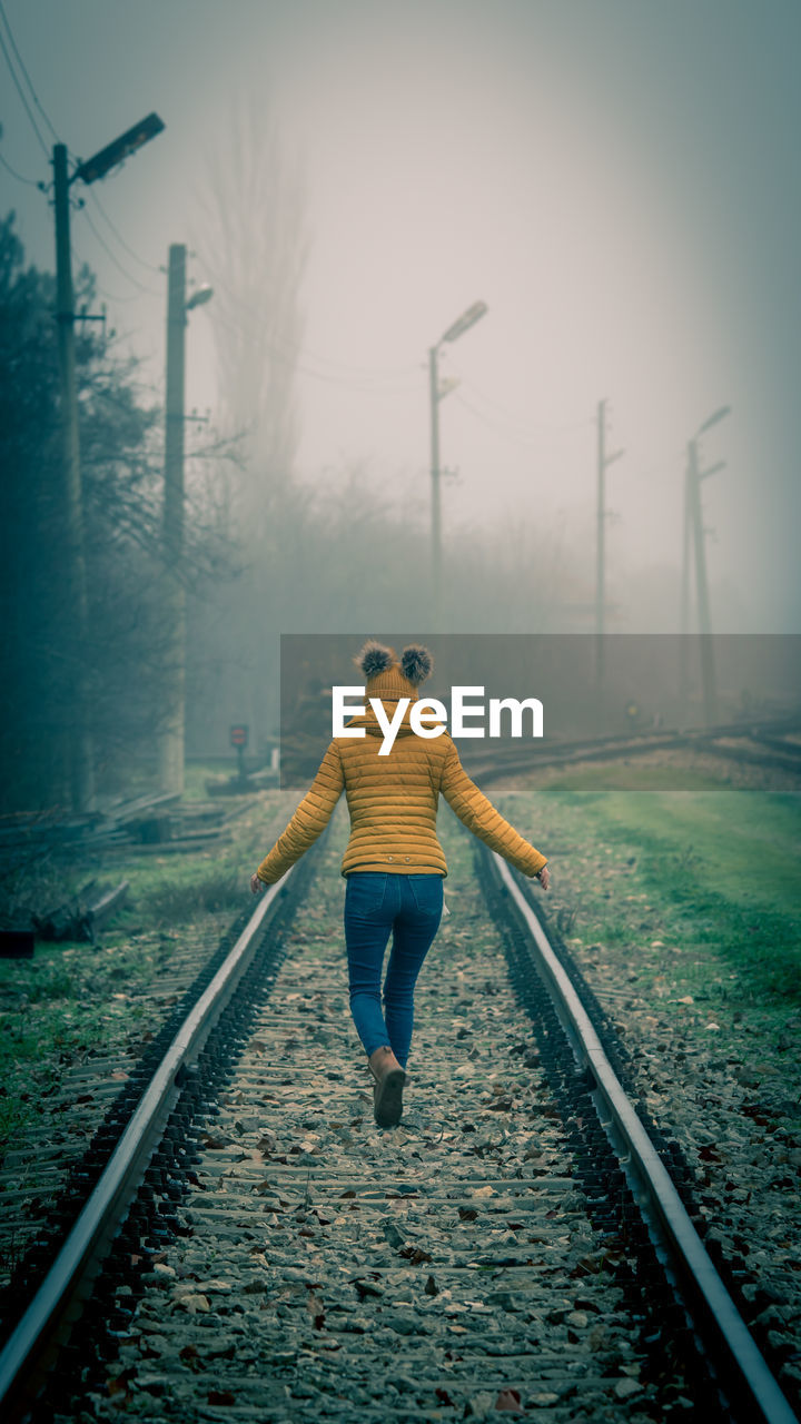 Rear view of girl walking on railroad track