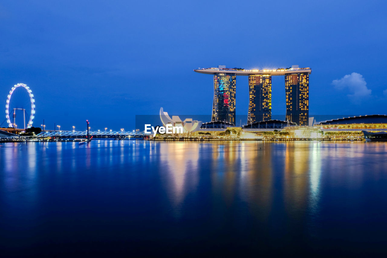 Marina Bay Sands By Bay Of Water Against Sky In City At Dusk