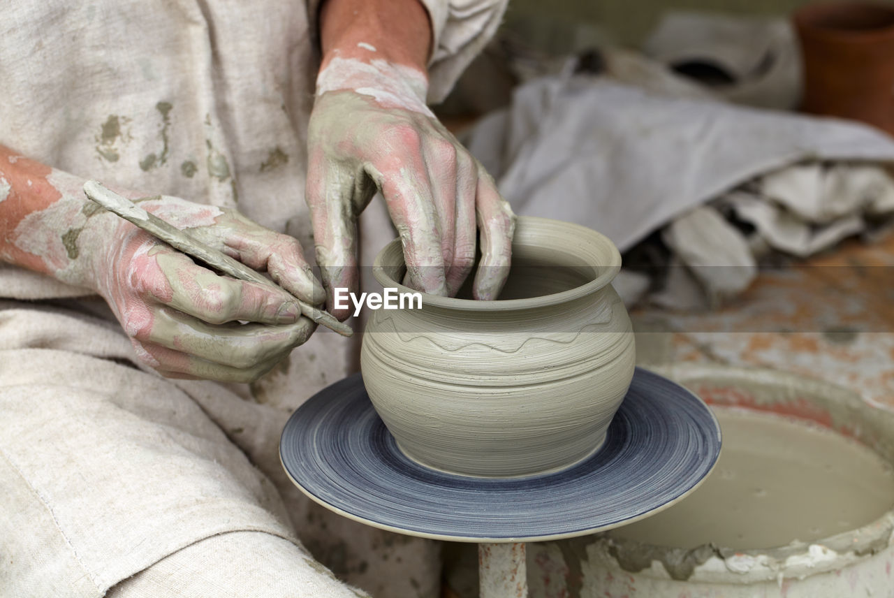 Midsection Of Potter Making Clay Container At Workshop
