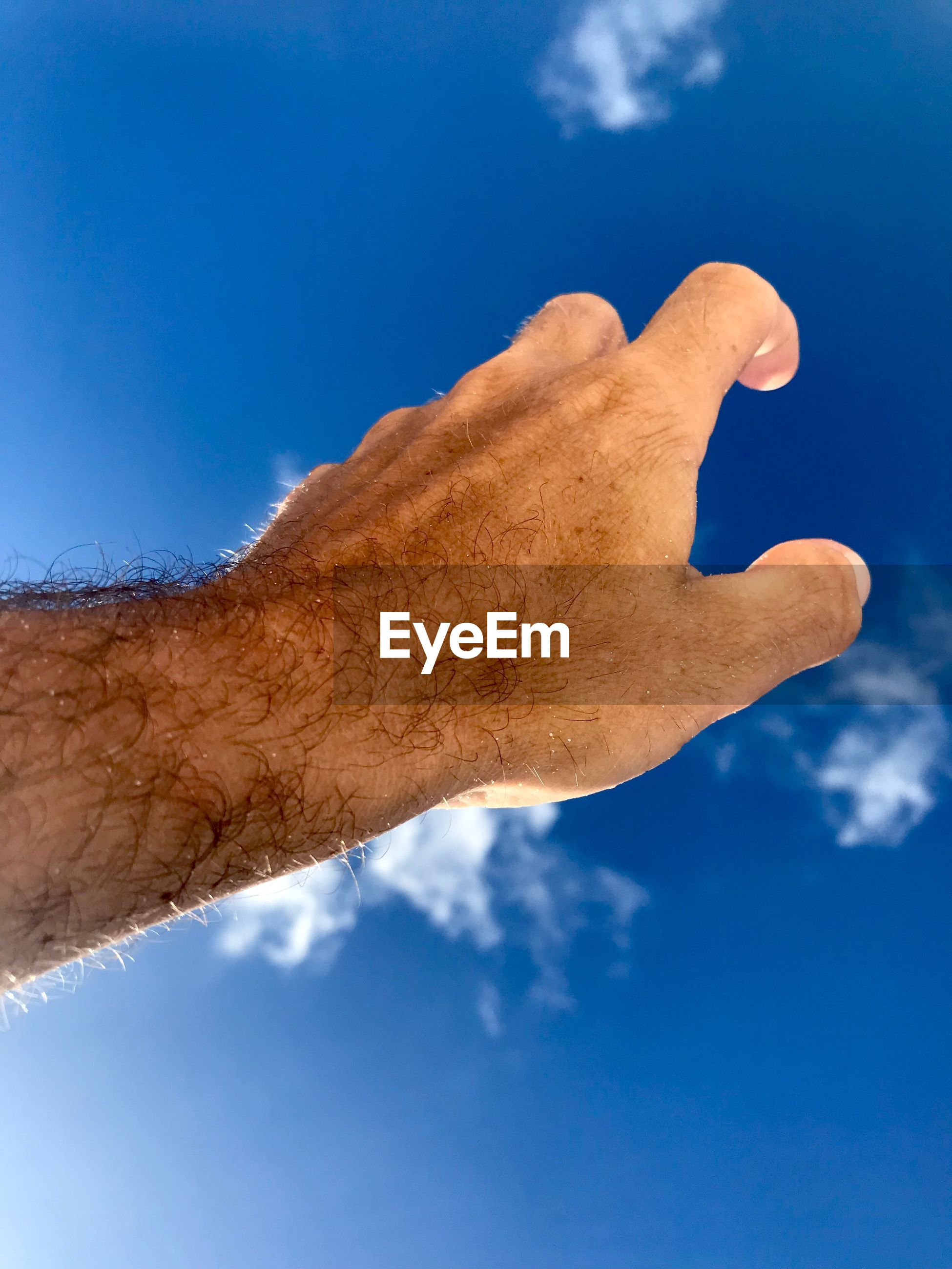 Low angle view of man hand reaching sky