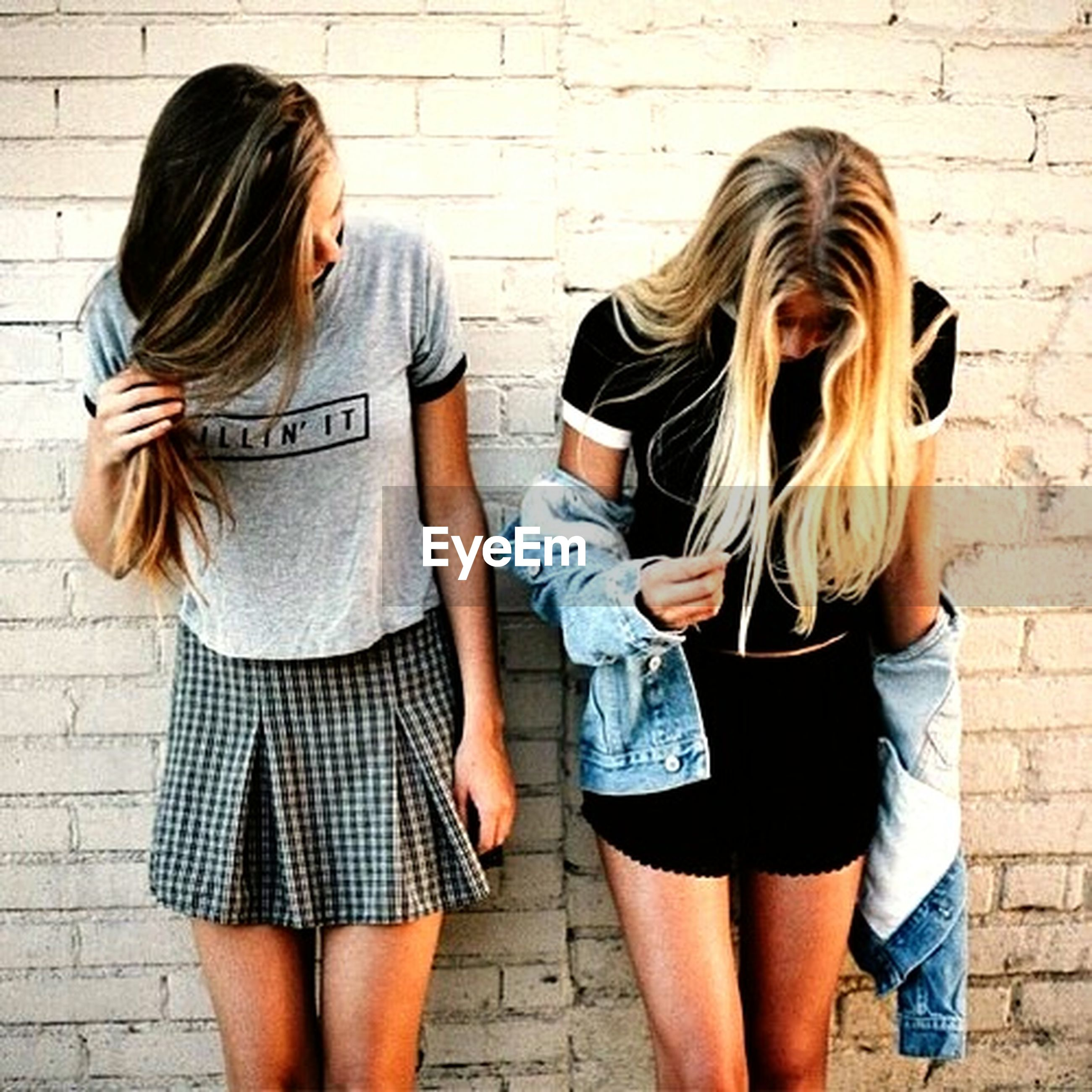 lifestyles, casual clothing, standing, person, togetherness, leisure activity, bonding, love, young women, young adult, friendship, three quarter length, long hair, front view, wall - building feature, smiling, happiness
