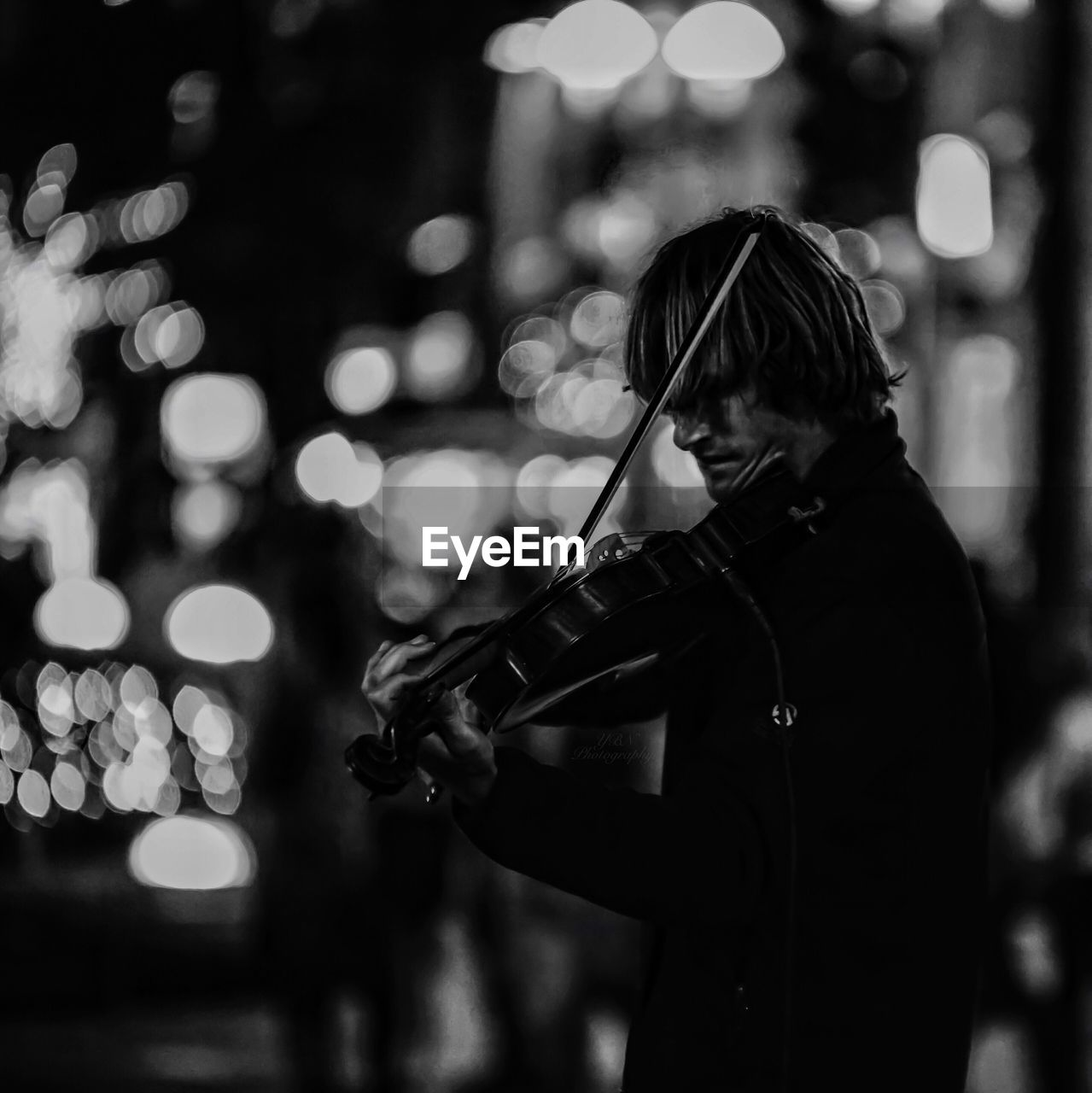 Side View Of Street Musician Playing Violin At Night