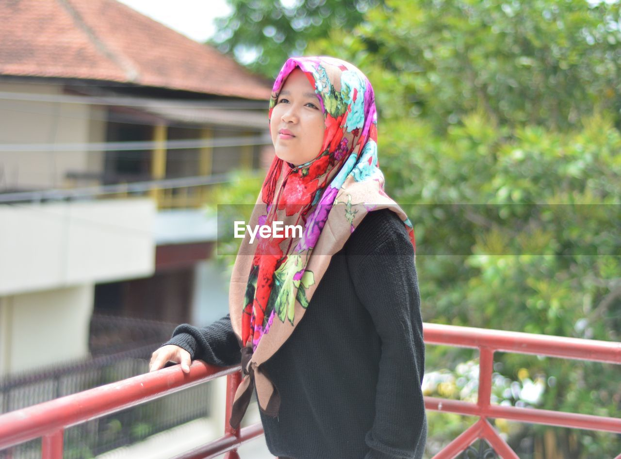 Woman wearing hijab standing by railing in balcony