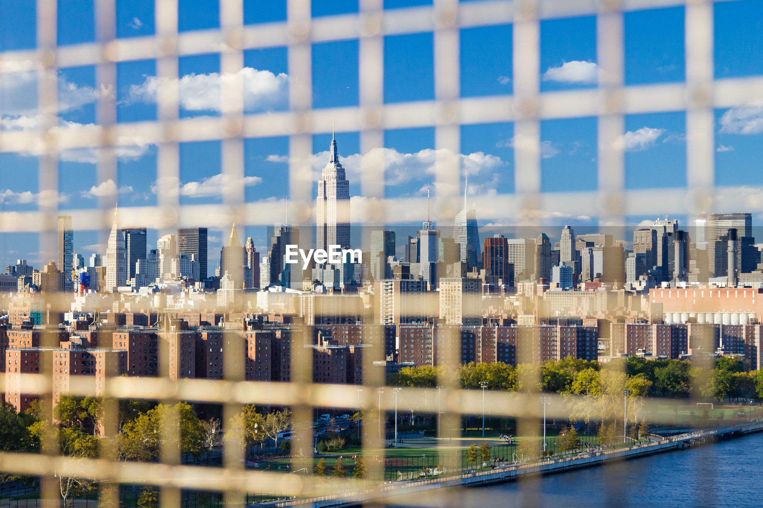 Buildings in city seen through fence
