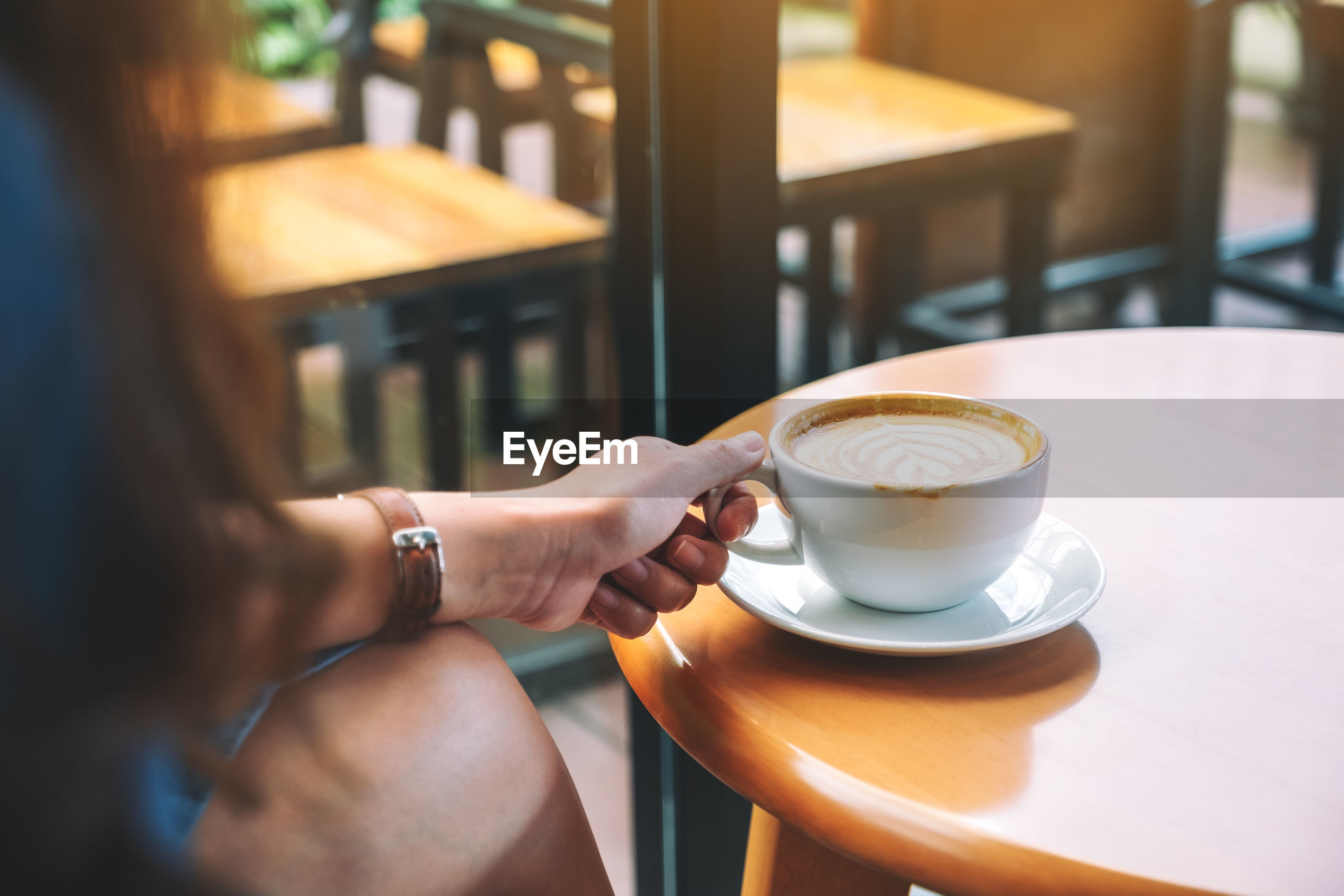 Cropped hand of woman holding coffee cup on table at cafe