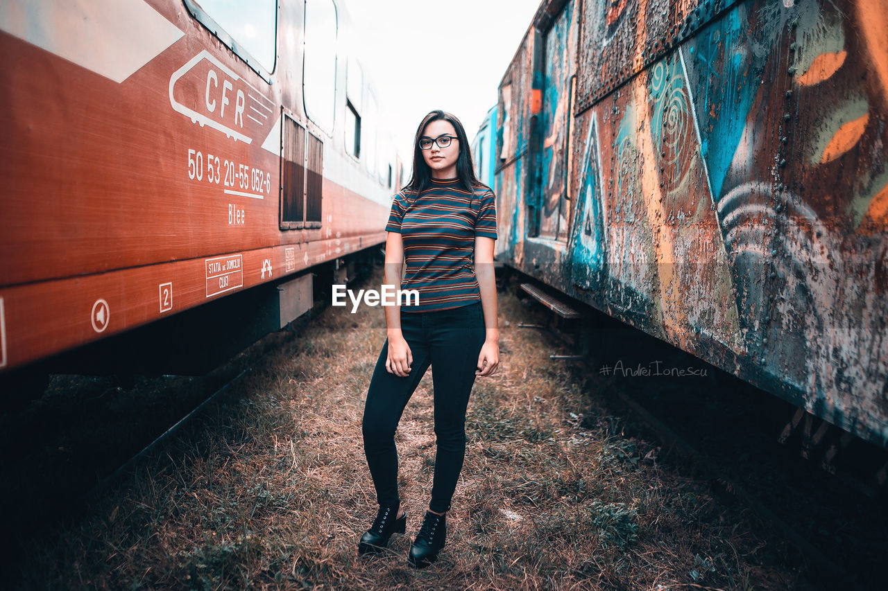 real people, one person, full length, transportation, standing, casual clothing, railroad track, front view, looking at camera, portrait, train - vehicle, leisure activity, young adult, lifestyles, outdoors, day, young women, beautiful woman, adult, people