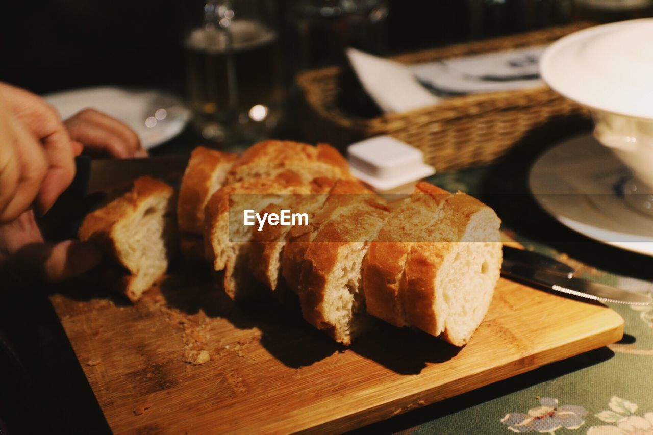 food and drink, food, one person, human hand, hand, indoors, real people, freshness, human body part, bread, unrecognizable person, holding, table, close-up, focus on foreground, cutting board, ready-to-eat, wood - material, lifestyles, knife, finger, tray, french food, temptation, breakfast