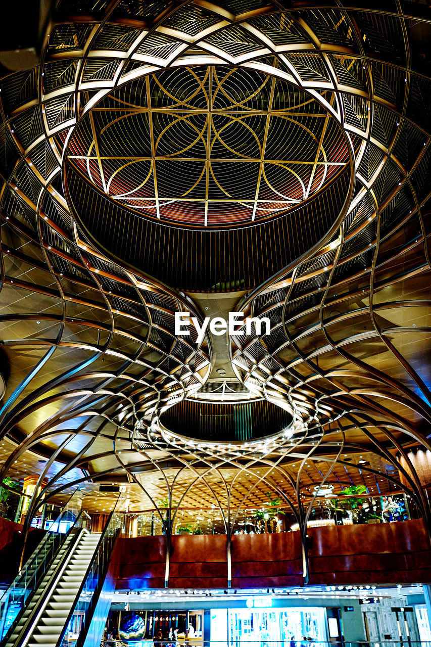 architecture, indoors, illuminated, no people, built structure, low angle view, ceiling, pattern, metal, lighting equipment, night, design, hanging, light, modern, architecture and art, place of worship, empty, religion, luxury, ornate