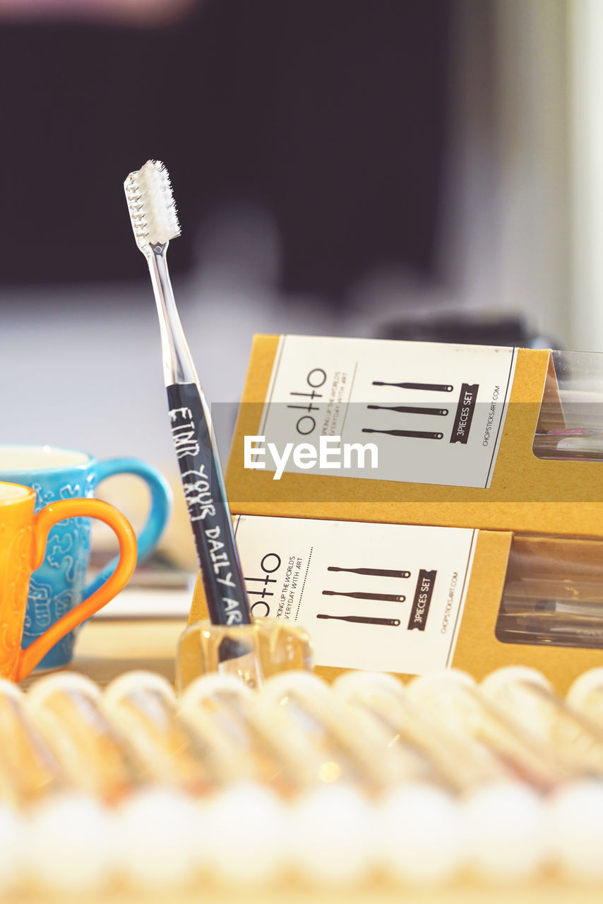 selective focus, indoors, still life, close-up, large group of objects, no people, healthcare and medicine, container, business, text, yellow, number, western script, choice, variation, table, group, store, equipment, medicine