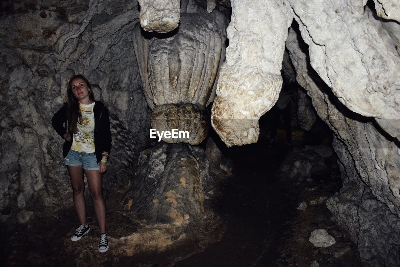Portrait of woman standing on rock in cave