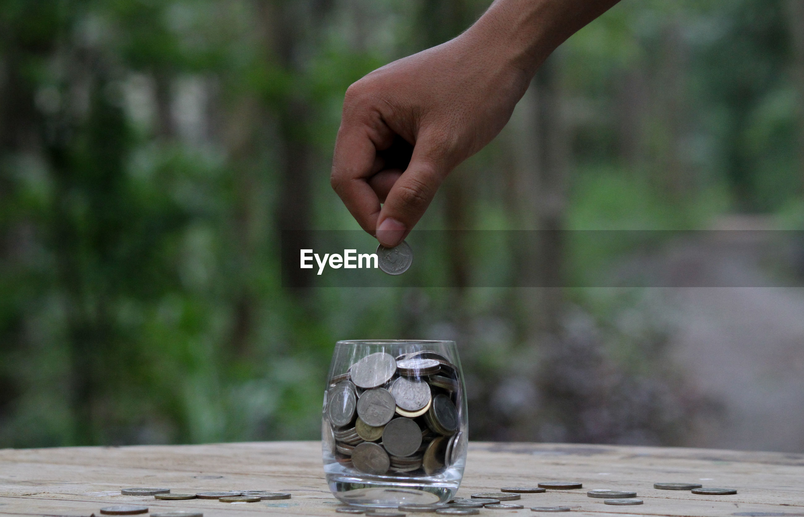 Cropped hand of man dropping coins in drinking glass on table against trees