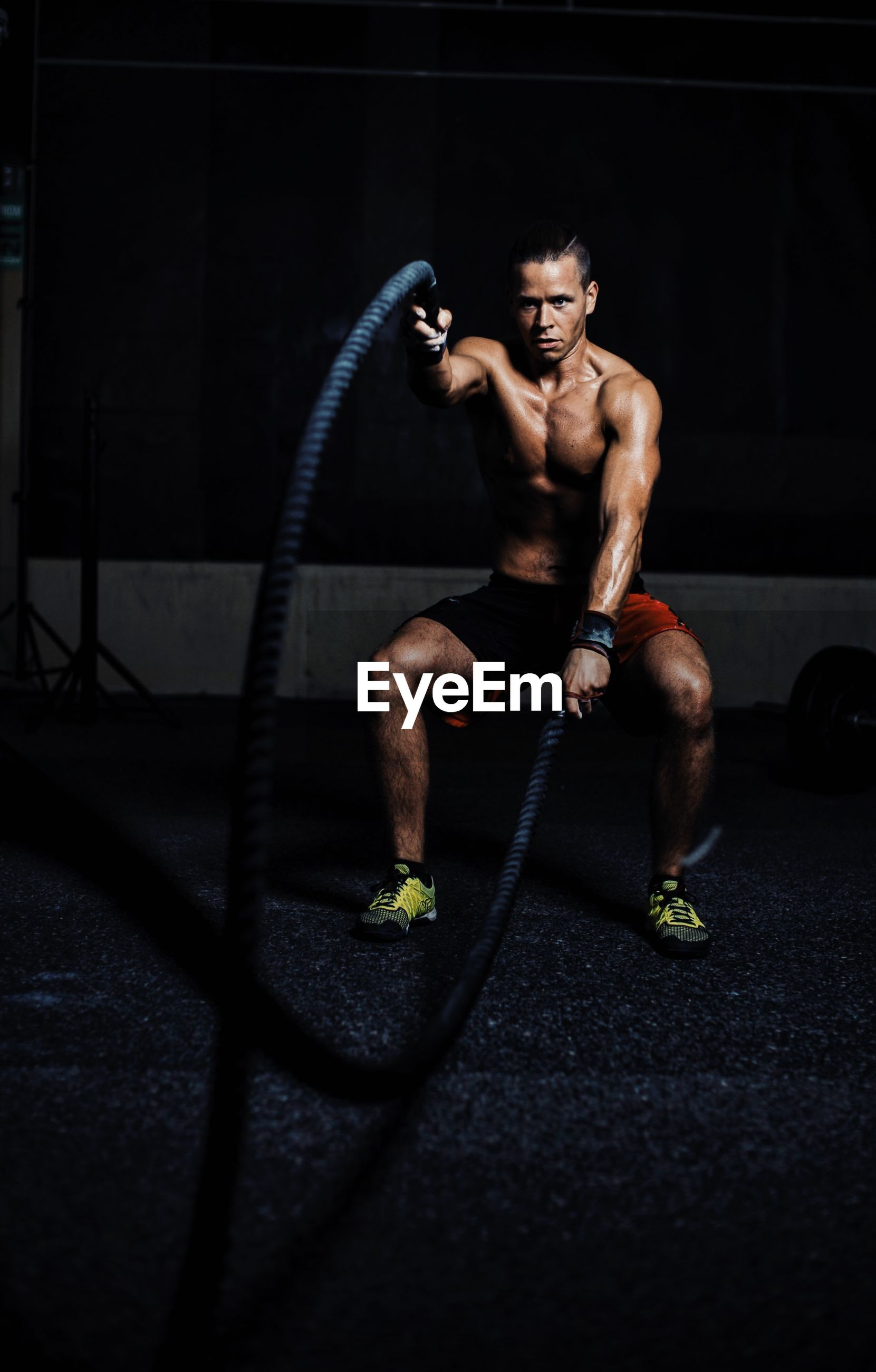 Portrait of muscular man exercising battle rope in gym