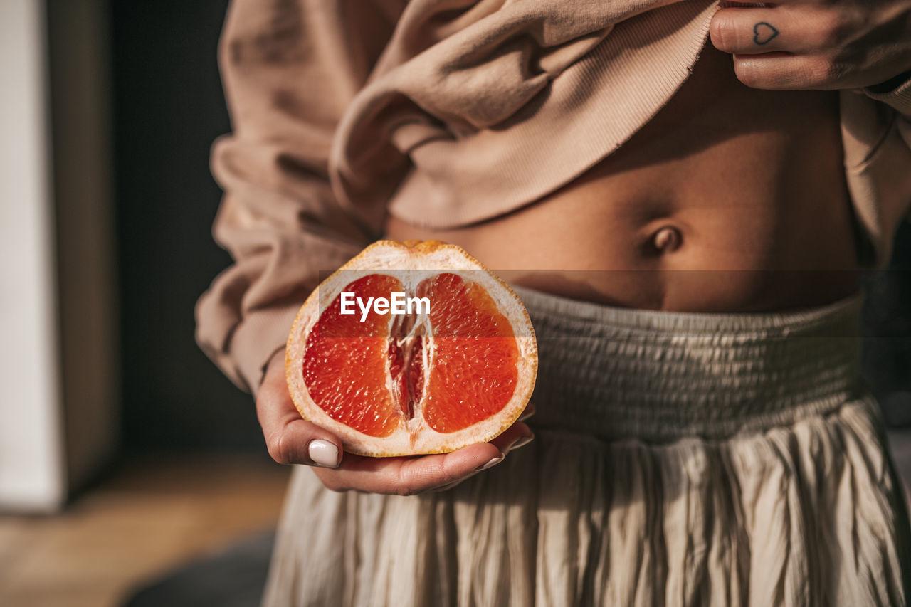 CLOSE-UP PORTRAIT OF WOMAN HOLDING FRUIT