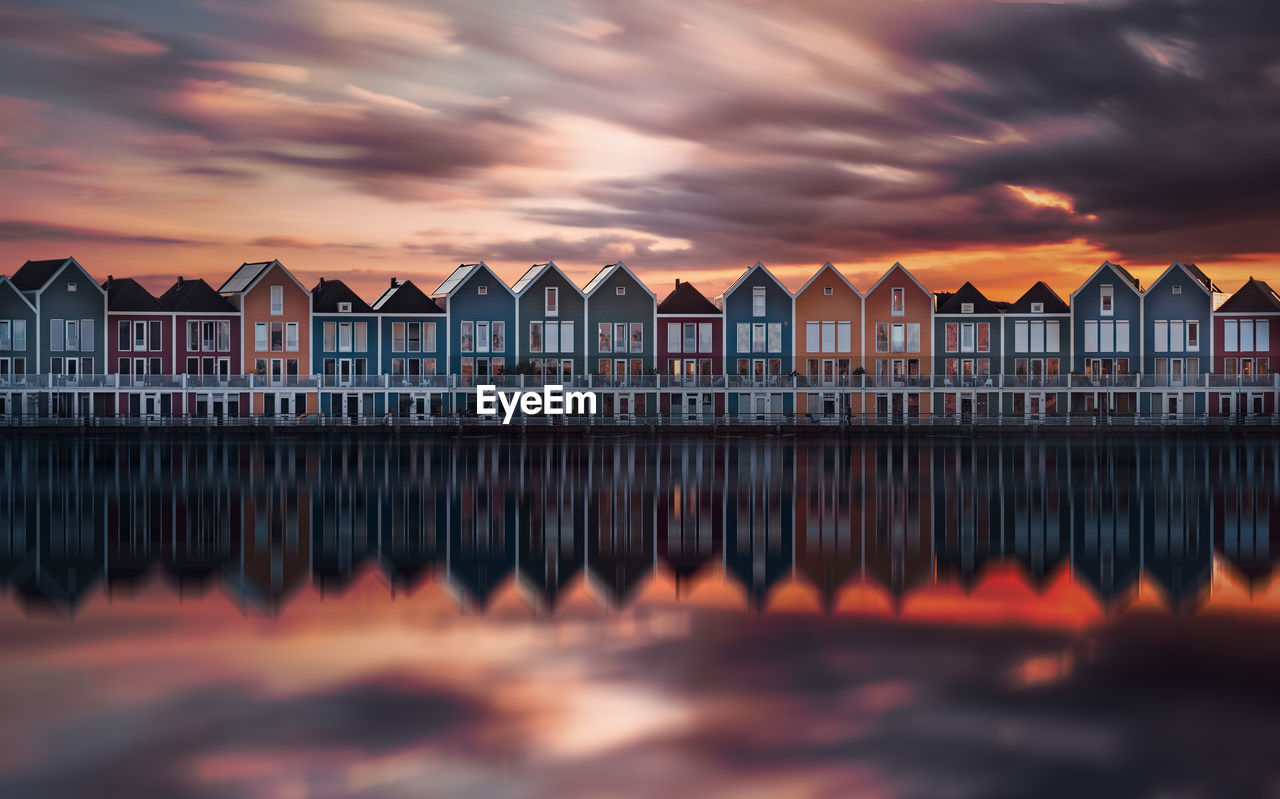 Panoramic View Of Houses By Sea Against Orange Sky