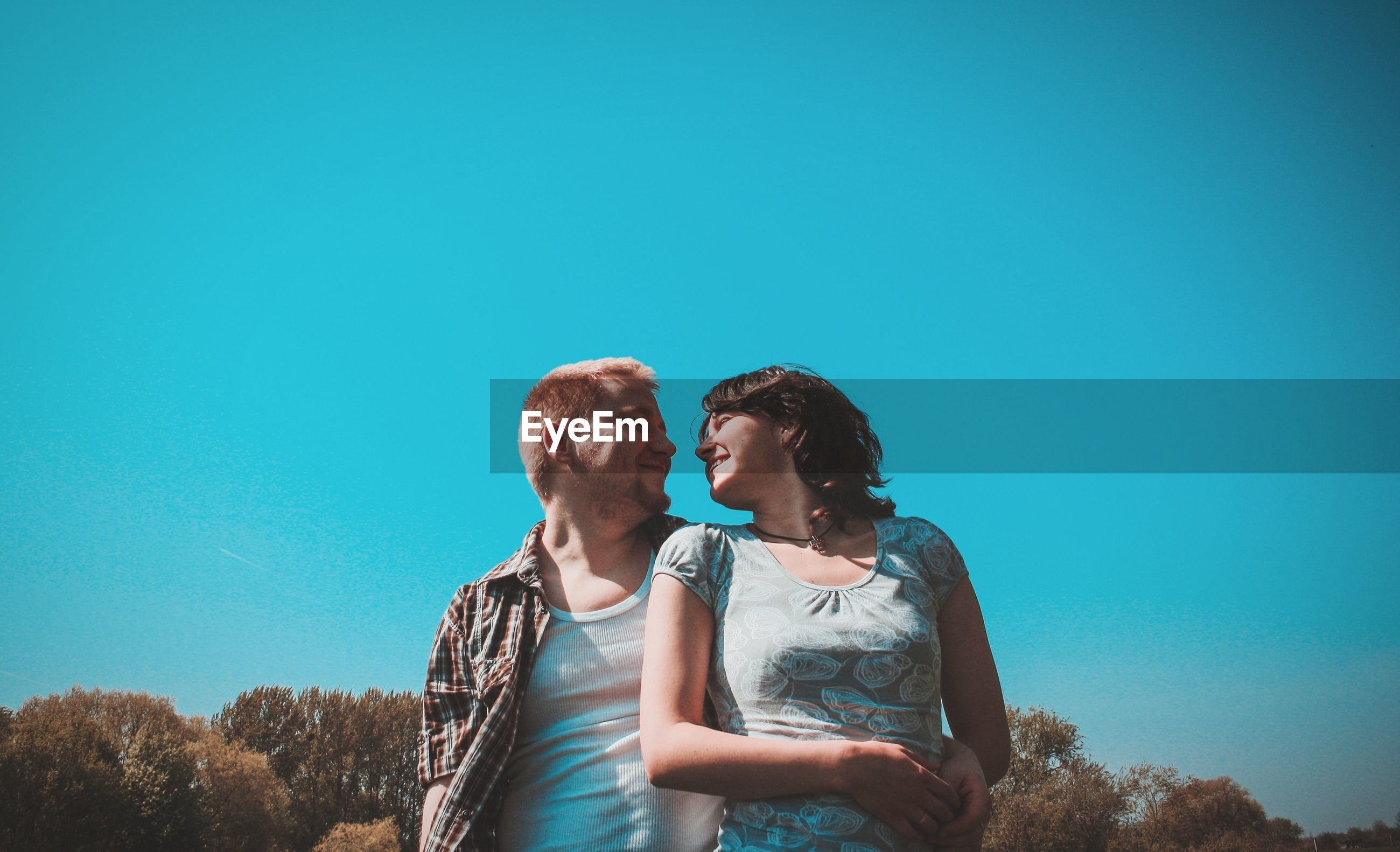 Young couple smiling against clear blue sky