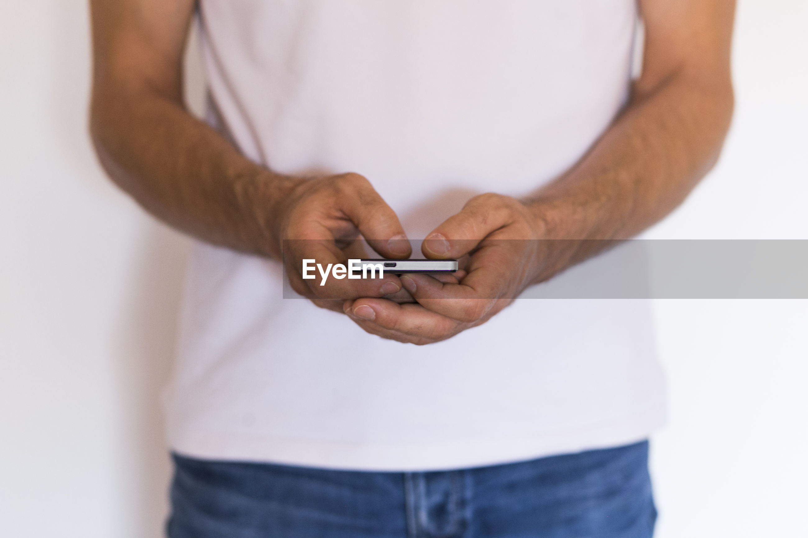 Midsection of man using smart phone against white background