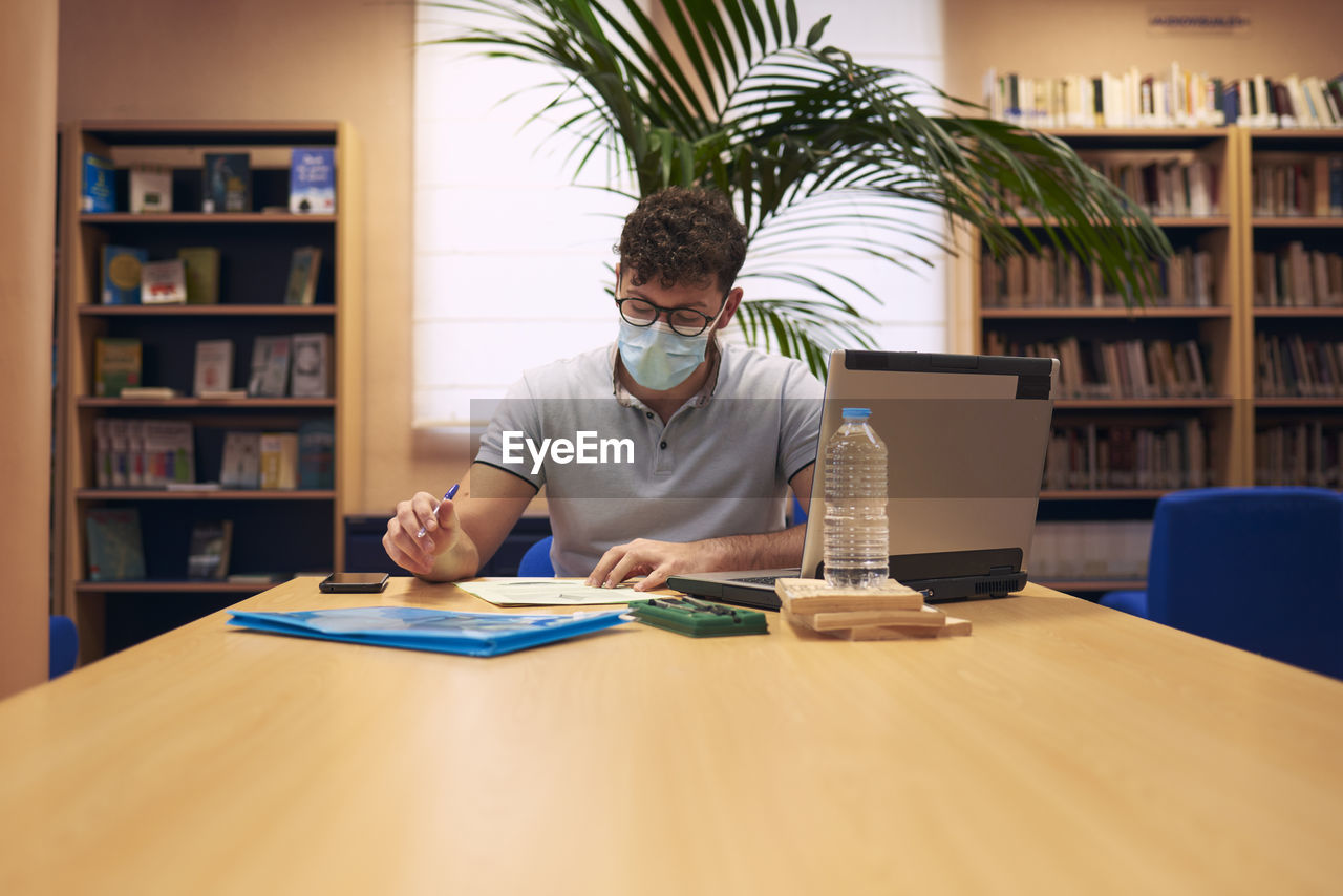A young boy with a mask sitting and working with his laptop in the library