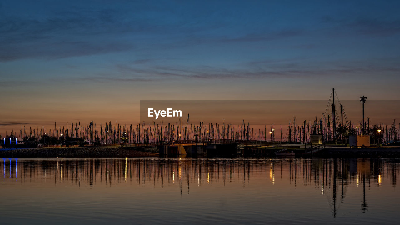 water, nautical vessel, reflection, waterfront, sky, sunset, moored, harbor, no people, nature, transportation, outdoors, mast, travel destinations, river, built structure, commercial dock, architecture, building exterior, beauty in nature, city, shipyard, day