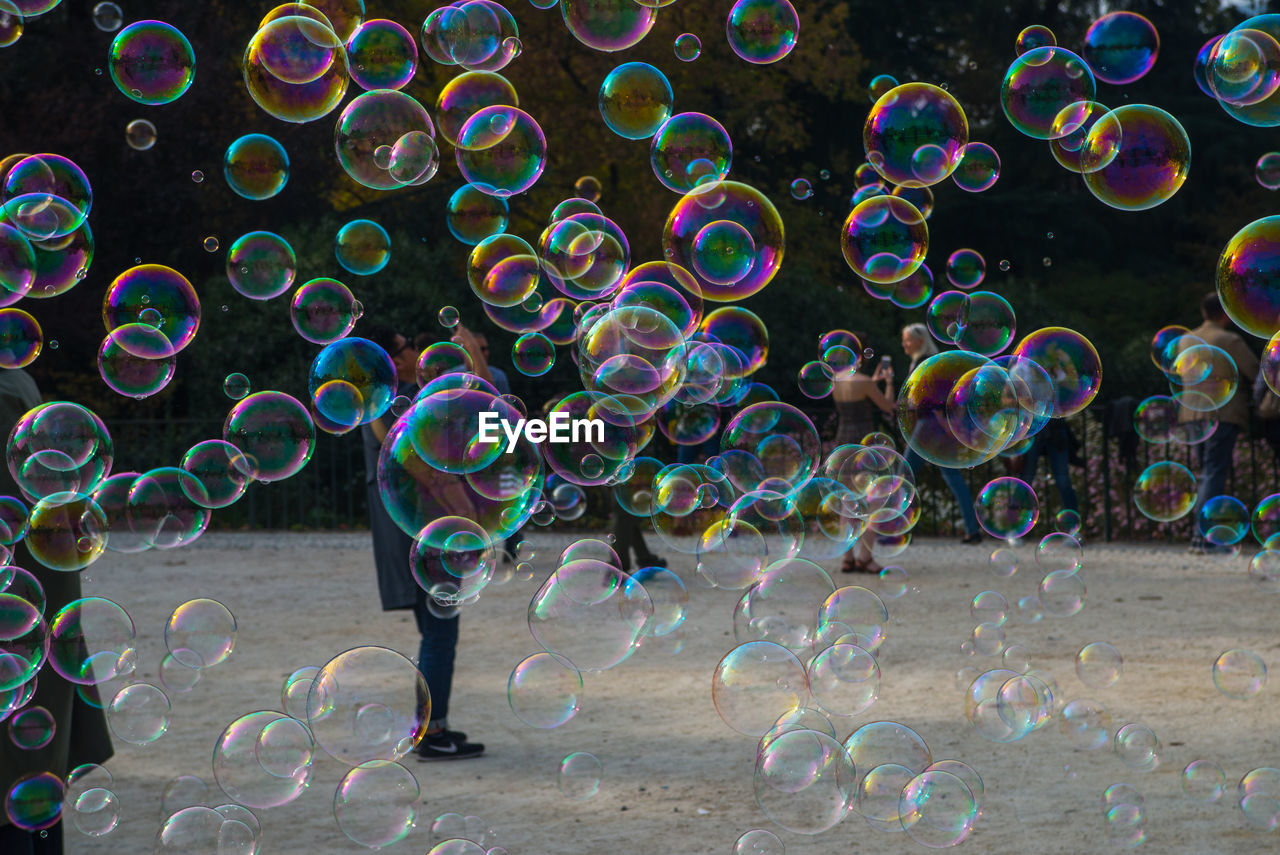 bubble, fragility, vulnerability, soap sud, transparent, bubble wand, motion, multi colored, nature, mid-air, lightweight, real people, day, blowing, leisure activity, one person, standing, outdoors, lifestyles