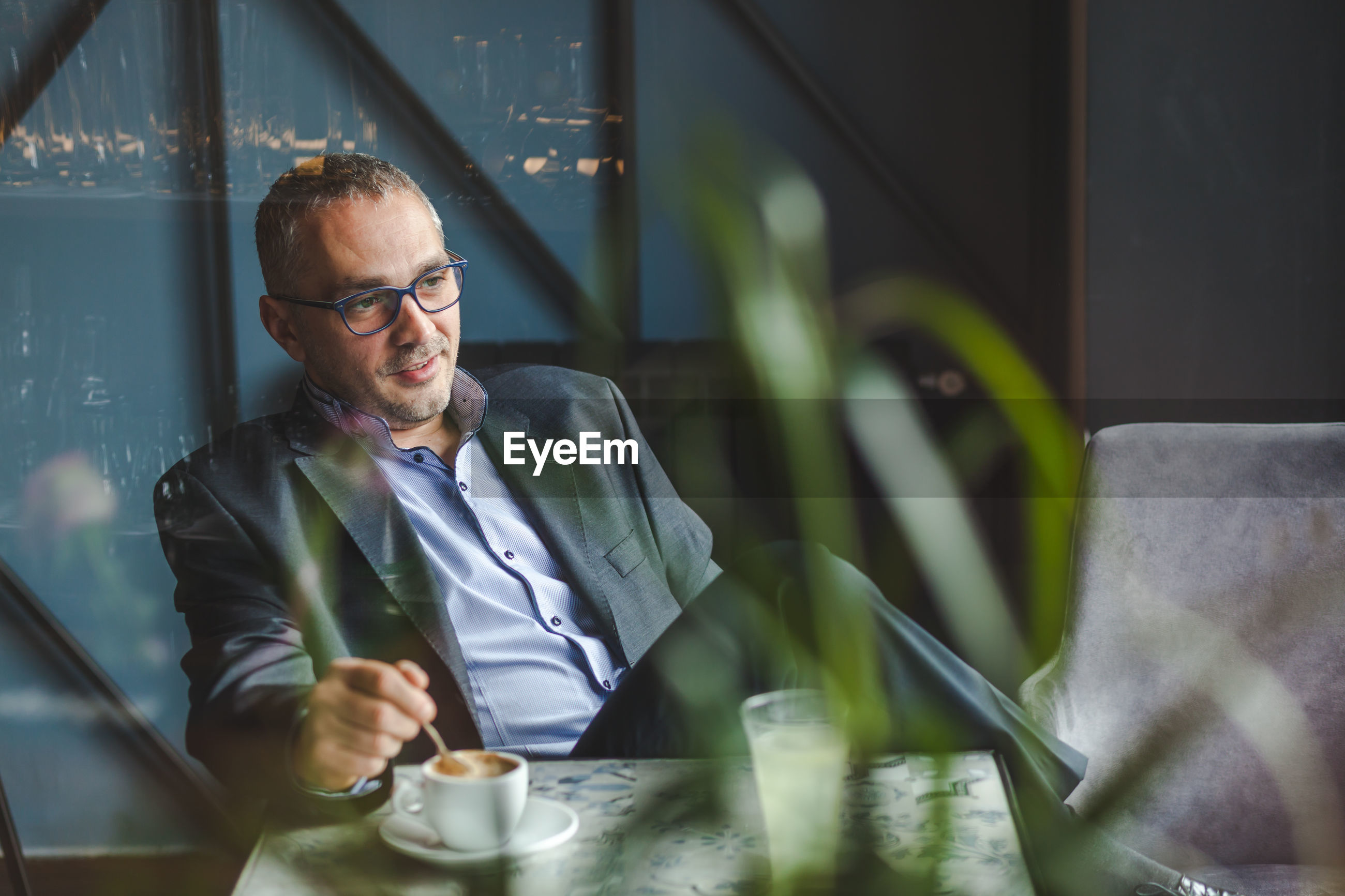 Businessman with coffee cup on table sitting in cafe