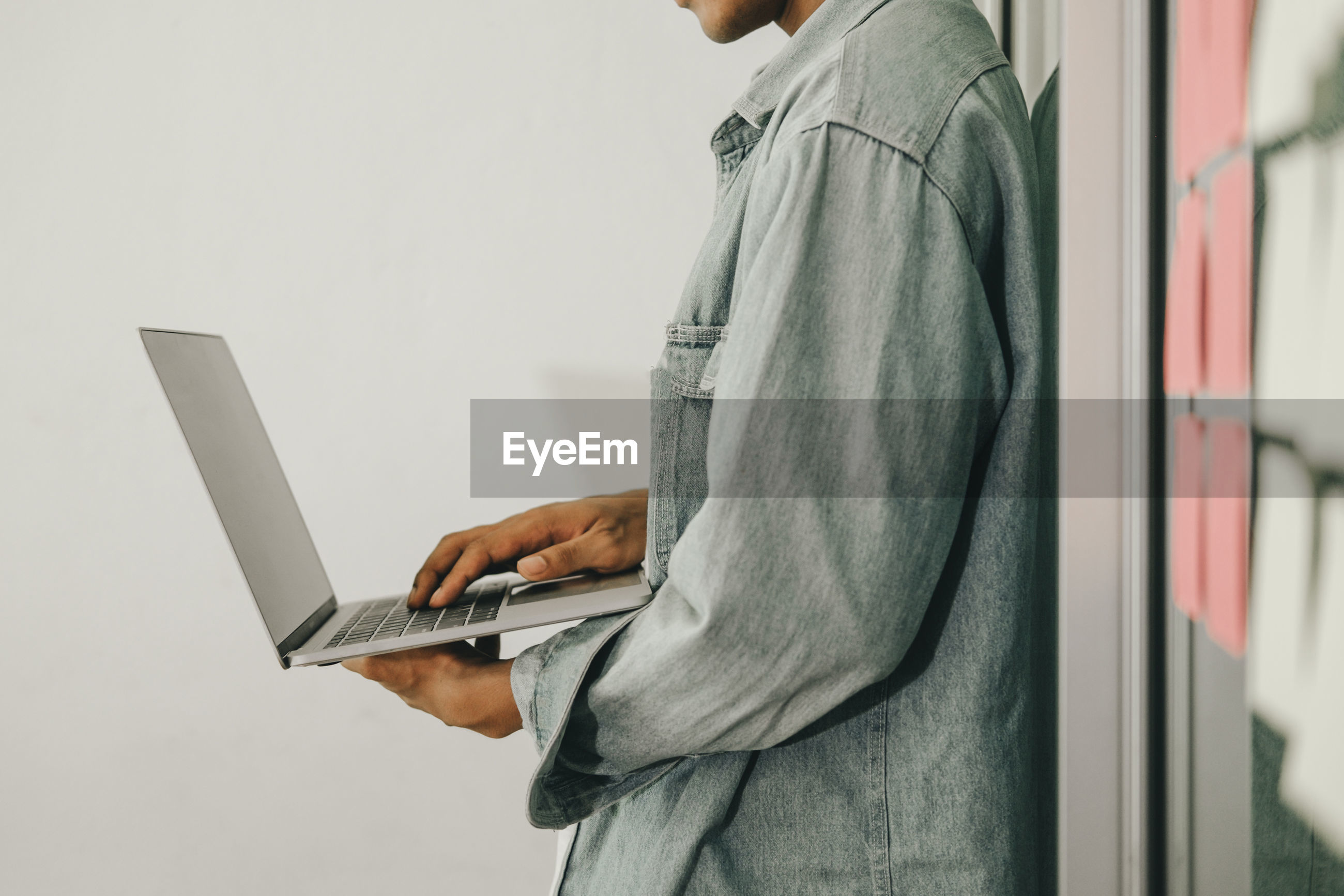 Midsection of man using laptop in office