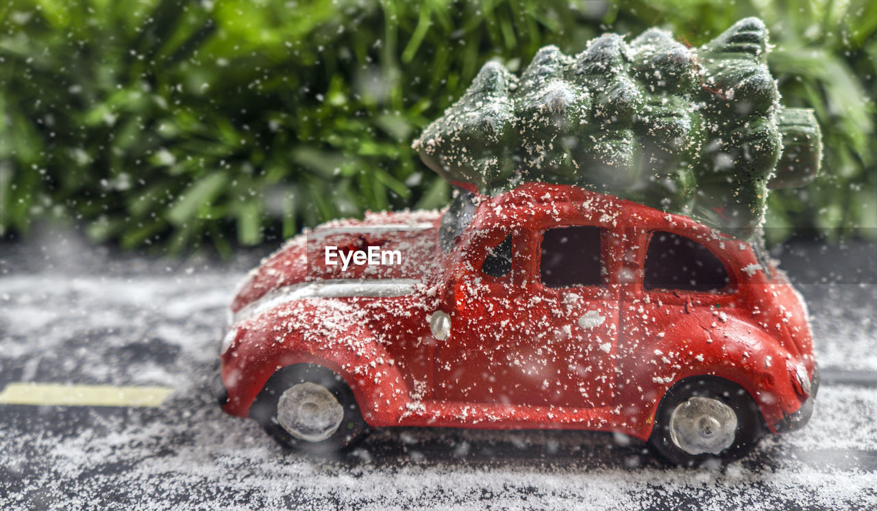 transportation, red, nature, mode of transportation, focus on foreground, motor vehicle, car, water, day, no people, motion, snow, land vehicle, winter, toy, close-up, wet, snowing, rainy season