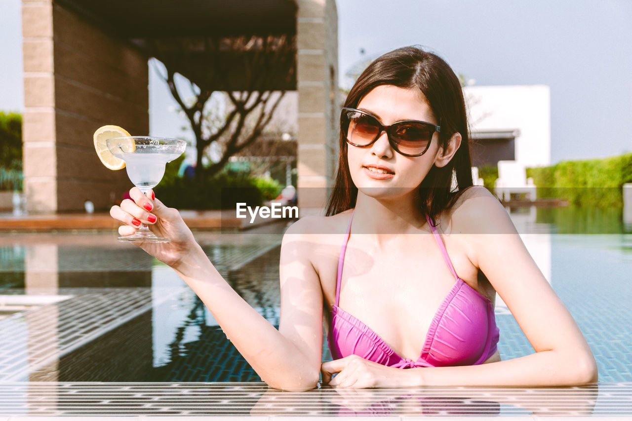 glasses, real people, one person, water, women, lifestyles, sunglasses, leisure activity, adult, young adult, holding, young women, front view, day, swimming pool, pool, focus on foreground, refreshment, fashion, glass, outdoors, beautiful woman