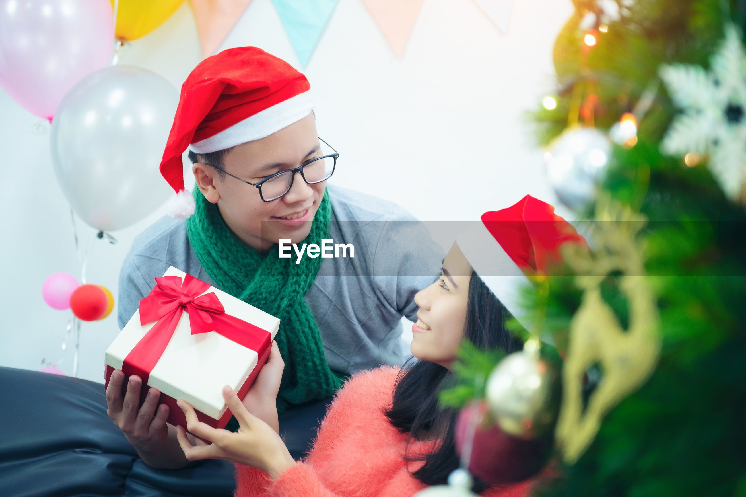 Man giving gift to girlfriend during christmas