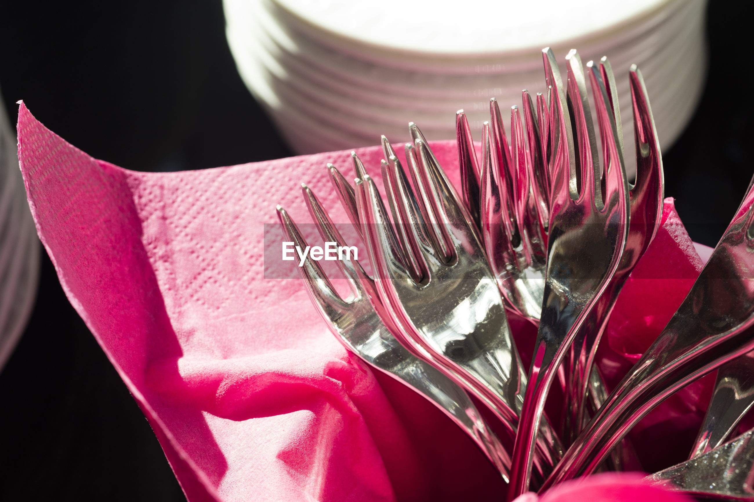 Close-up of forks by pink tissue by crockery against black background