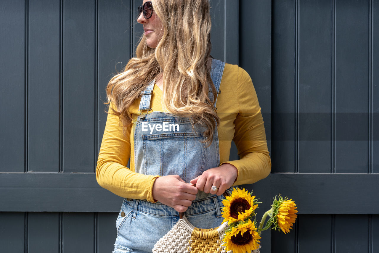 Woman holding yellow flowers in purse against wall