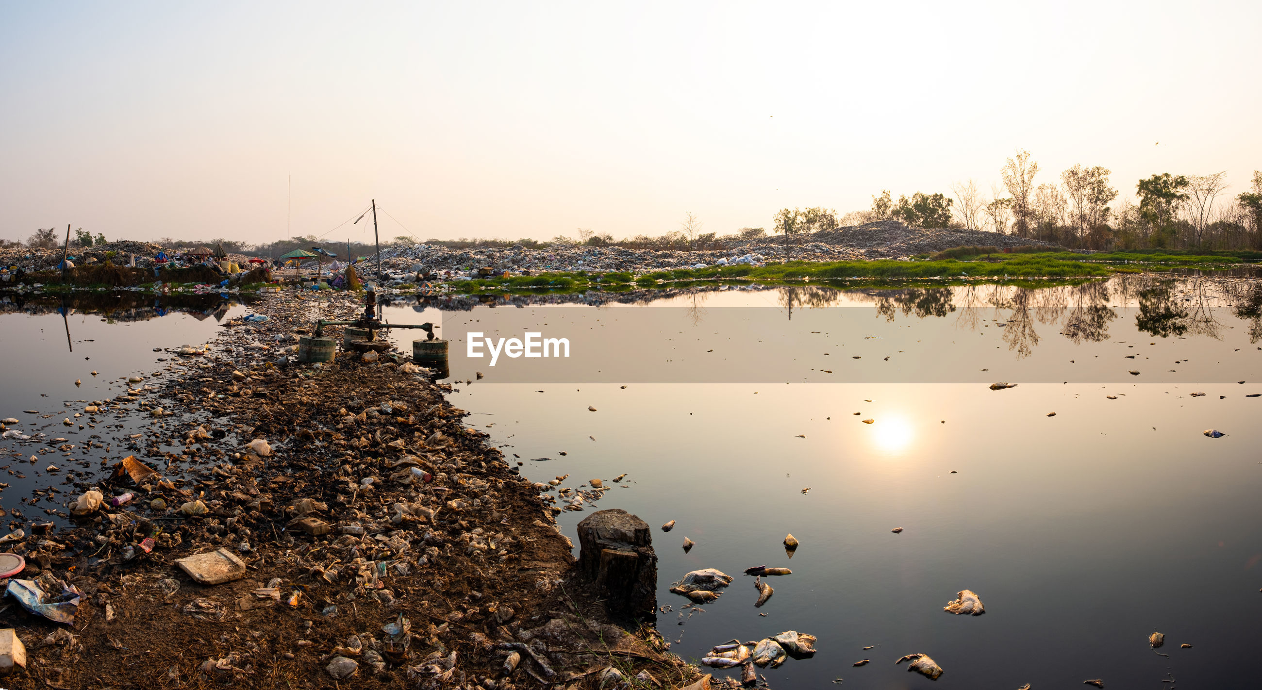 Polluted water and mountain large garbage pile and pollution at the sun is setting in the background