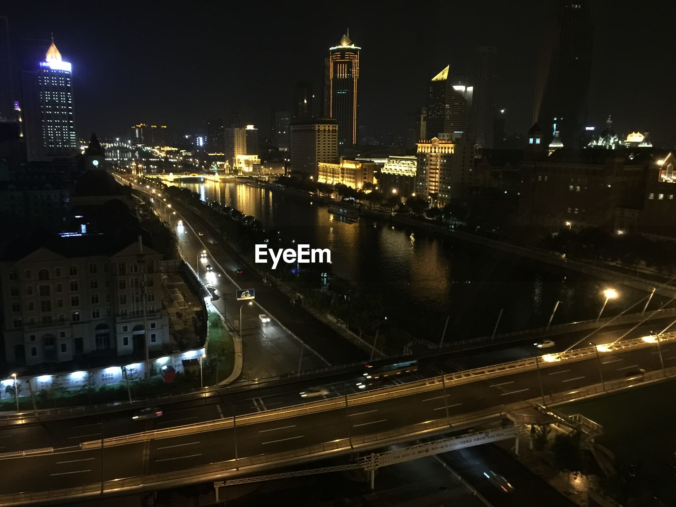 High angle view of river along buildings at night