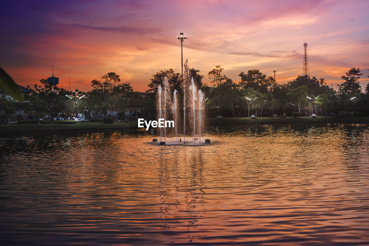water, fountain, sunset, sky, orange color, cloud - sky, spraying, splashing, travel destinations, waterfront, tree, architecture, travel, outdoors, tourism, reflection, built structure, statue, long exposure, nature, motion, no people, beauty in nature, building exterior, sculpture, scenics, illuminated, city, day