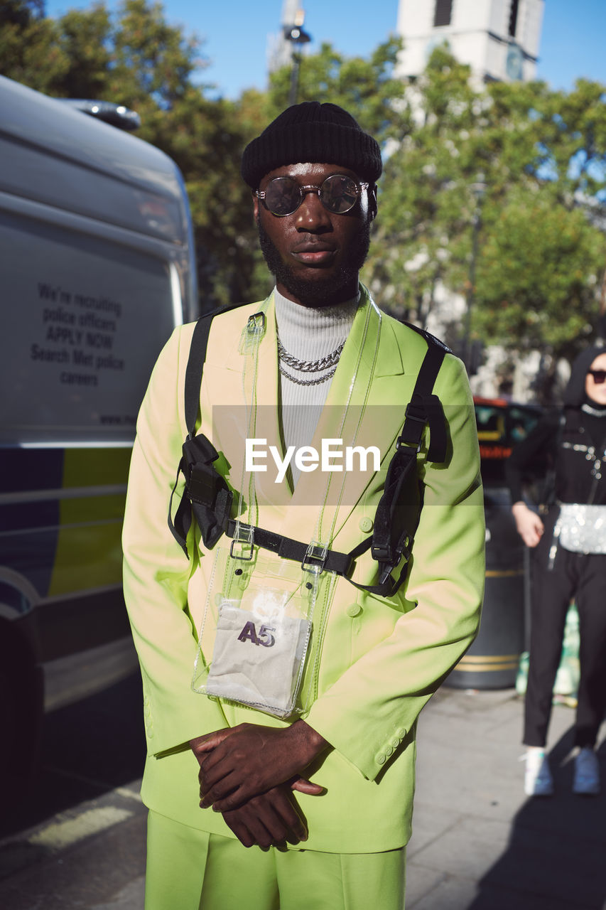 standing, real people, front view, looking at camera, one person, glasses, sunglasses, day, incidental people, portrait, men, focus on foreground, fashion, clothing, transportation, sunlight, males, three quarter length, waist up, outdoors, uniform