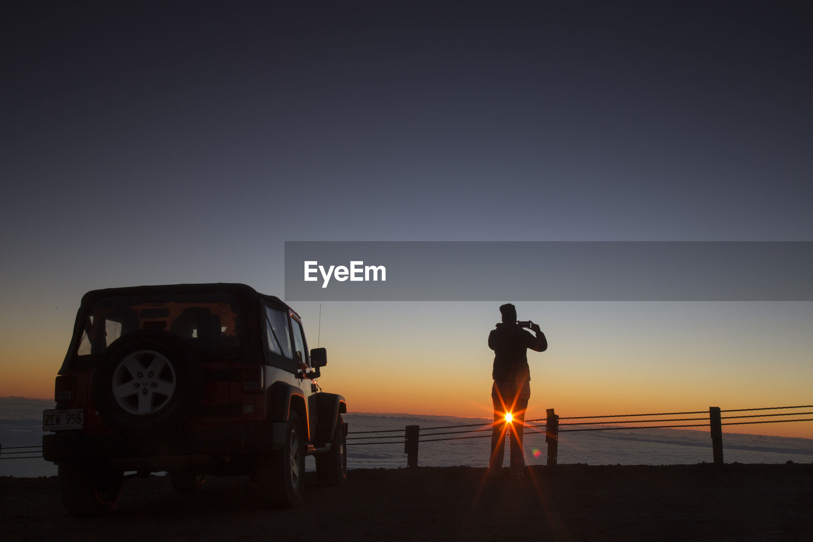 sunset, transportation, real people, silhouette, mode of transport, copy space, men, nature, sea, rear view, standing, clear sky, one person, land vehicle, sun, sky, full length, outdoors, beach, lifestyles, sand, one man only, day, people