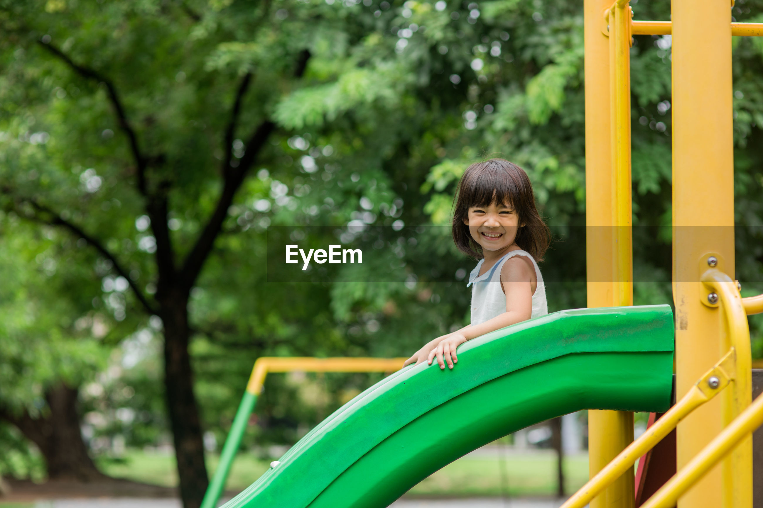 Full length of smiling girl looking away while moving on slide in playground