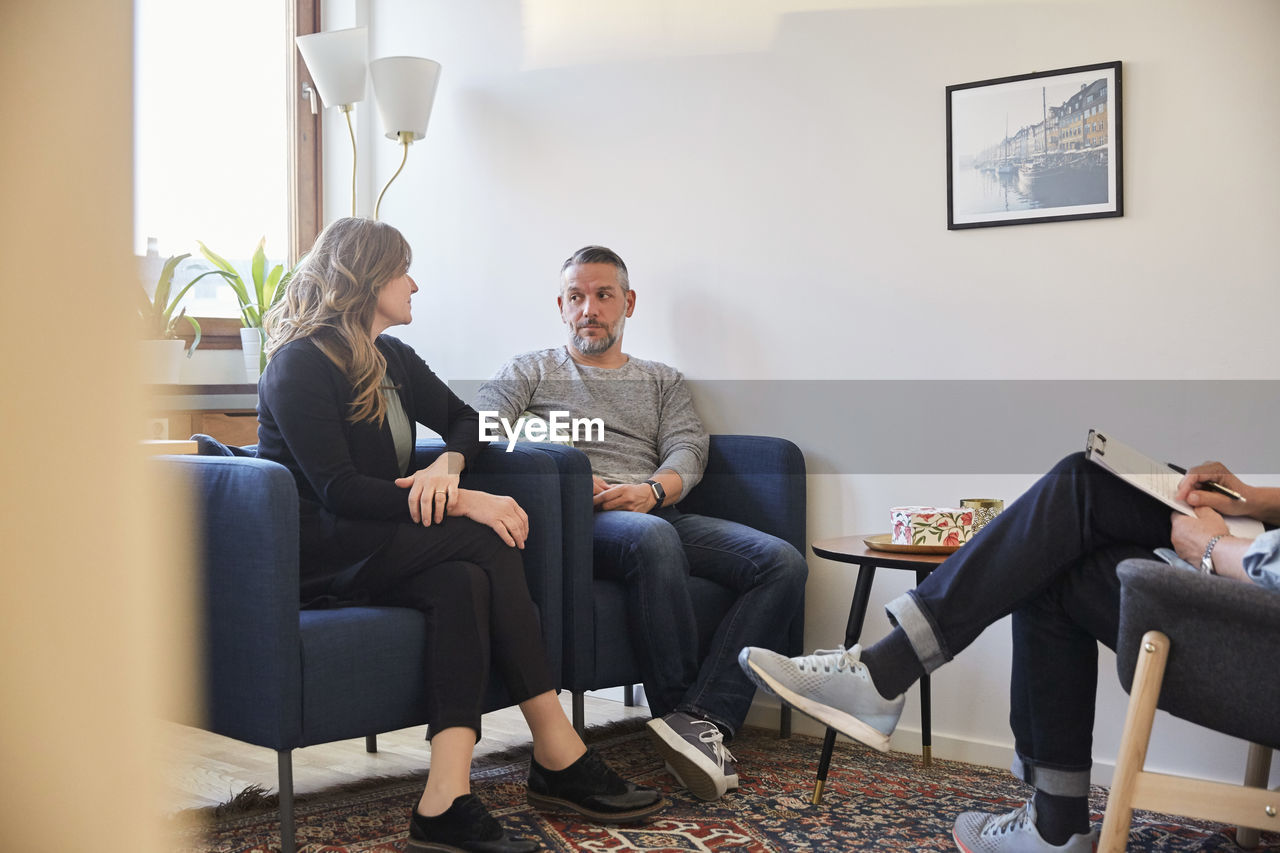 PEOPLE SITTING ON SOFA IN HOME
