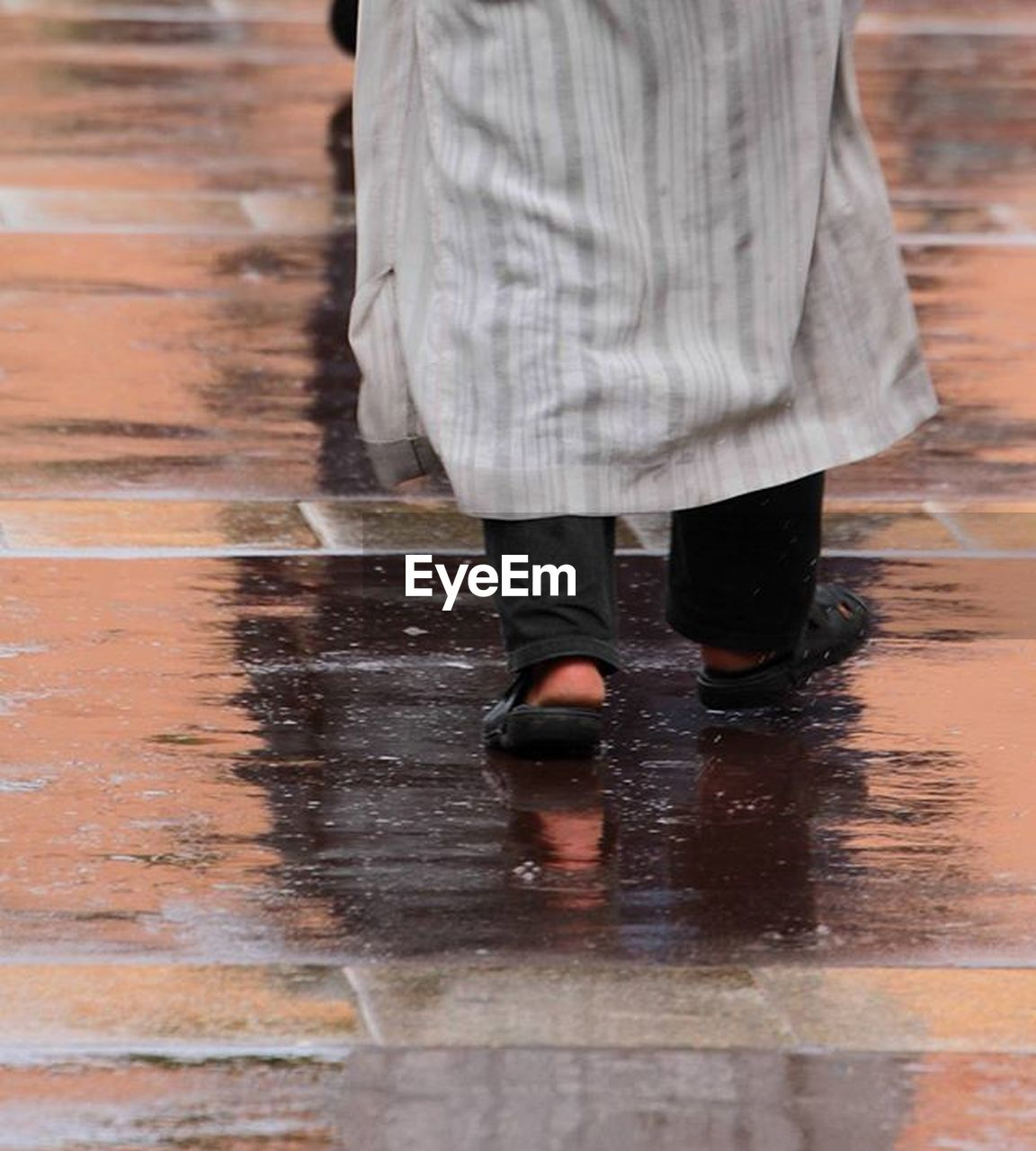 low section, walking, human leg, one person, motion, wet, shoe, human body part, standing, adult, city, body part, rain, day, water, casual clothing, reflection, footpath, outdoors, rainy season