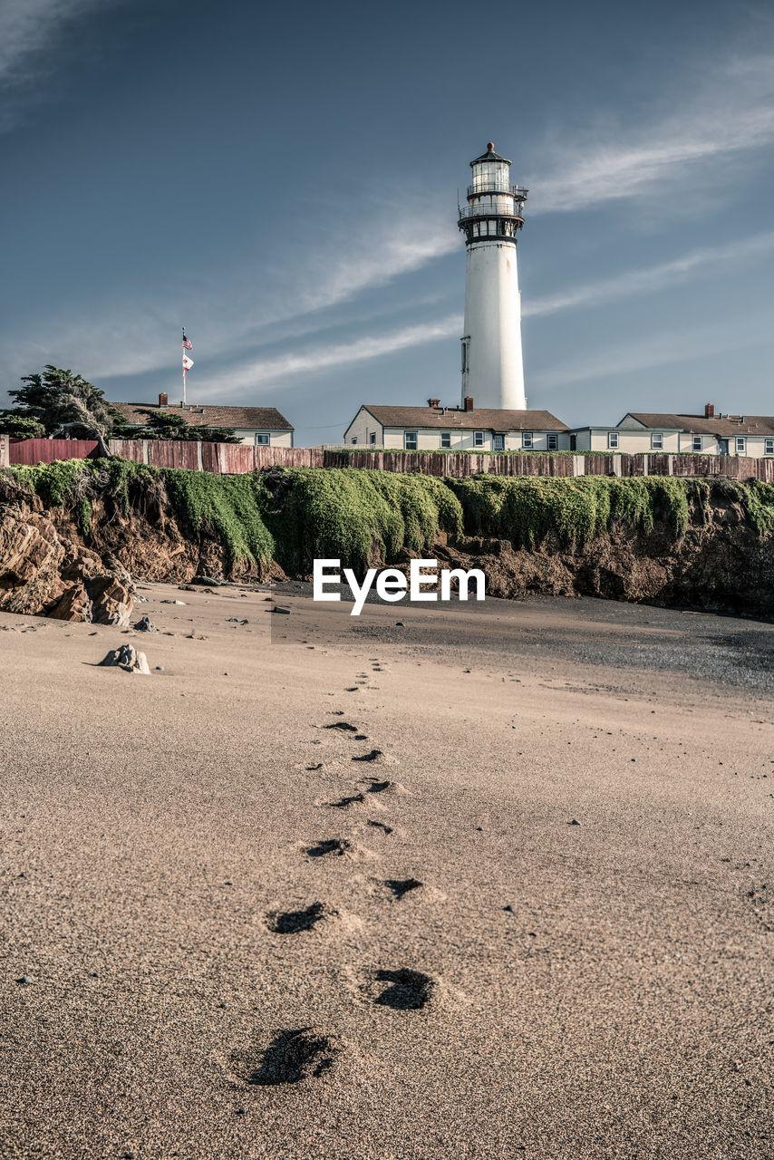 Pigeon point lighthouse by sandy beach against sky