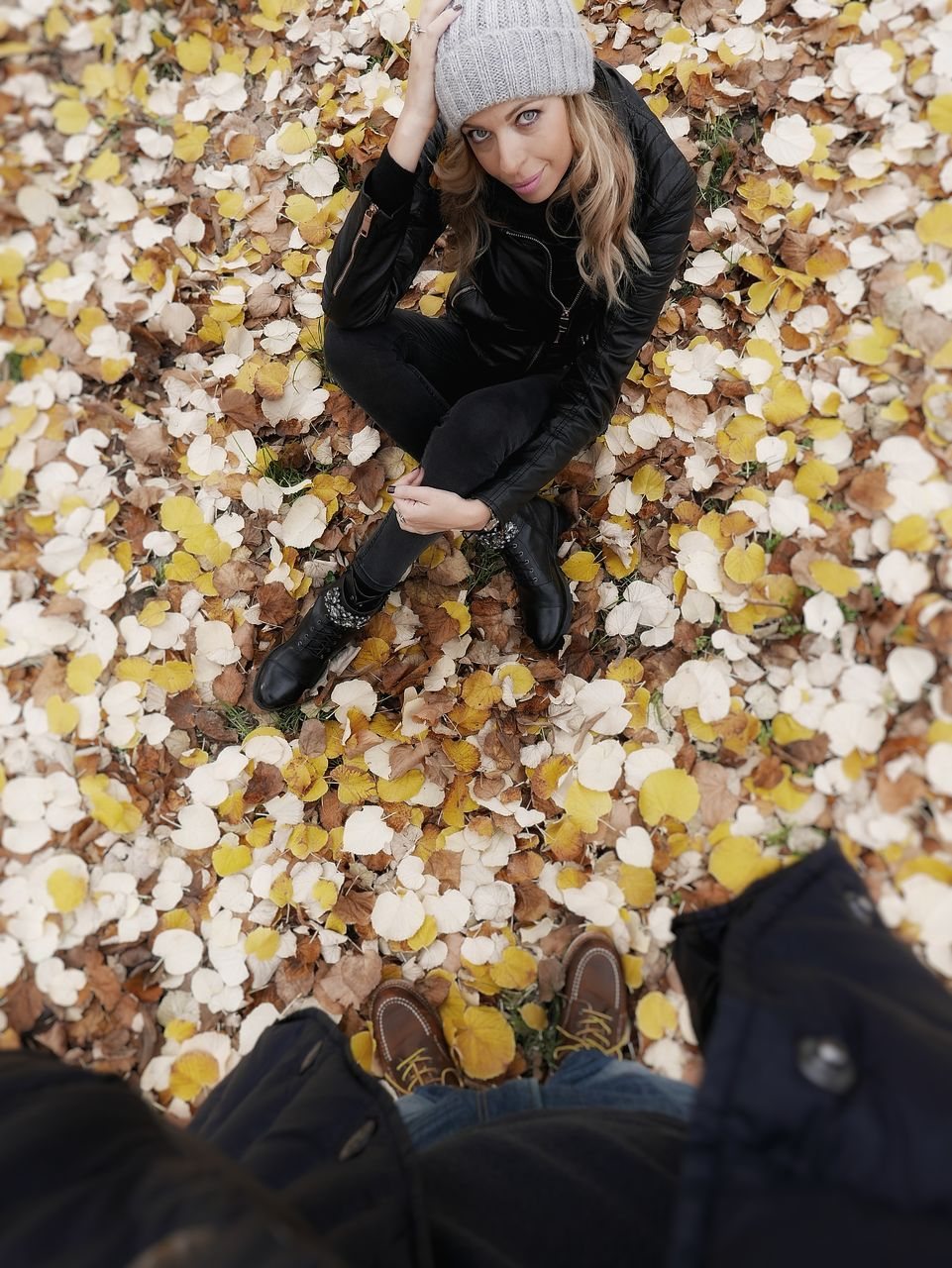 High angle portrait of young woman sitting on field during autumn