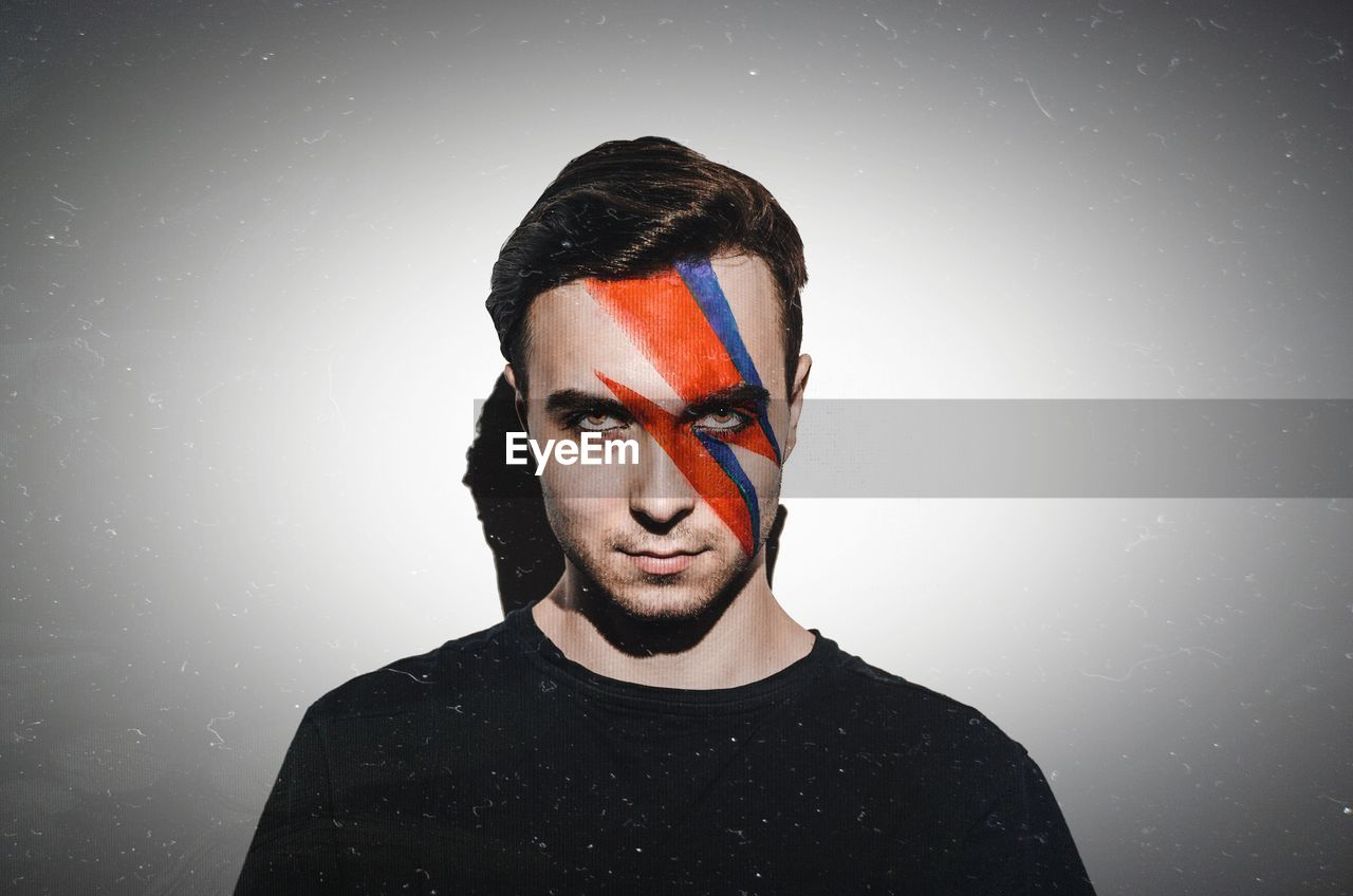 Portrait Of Young Man With Face Paint Against Gray Background