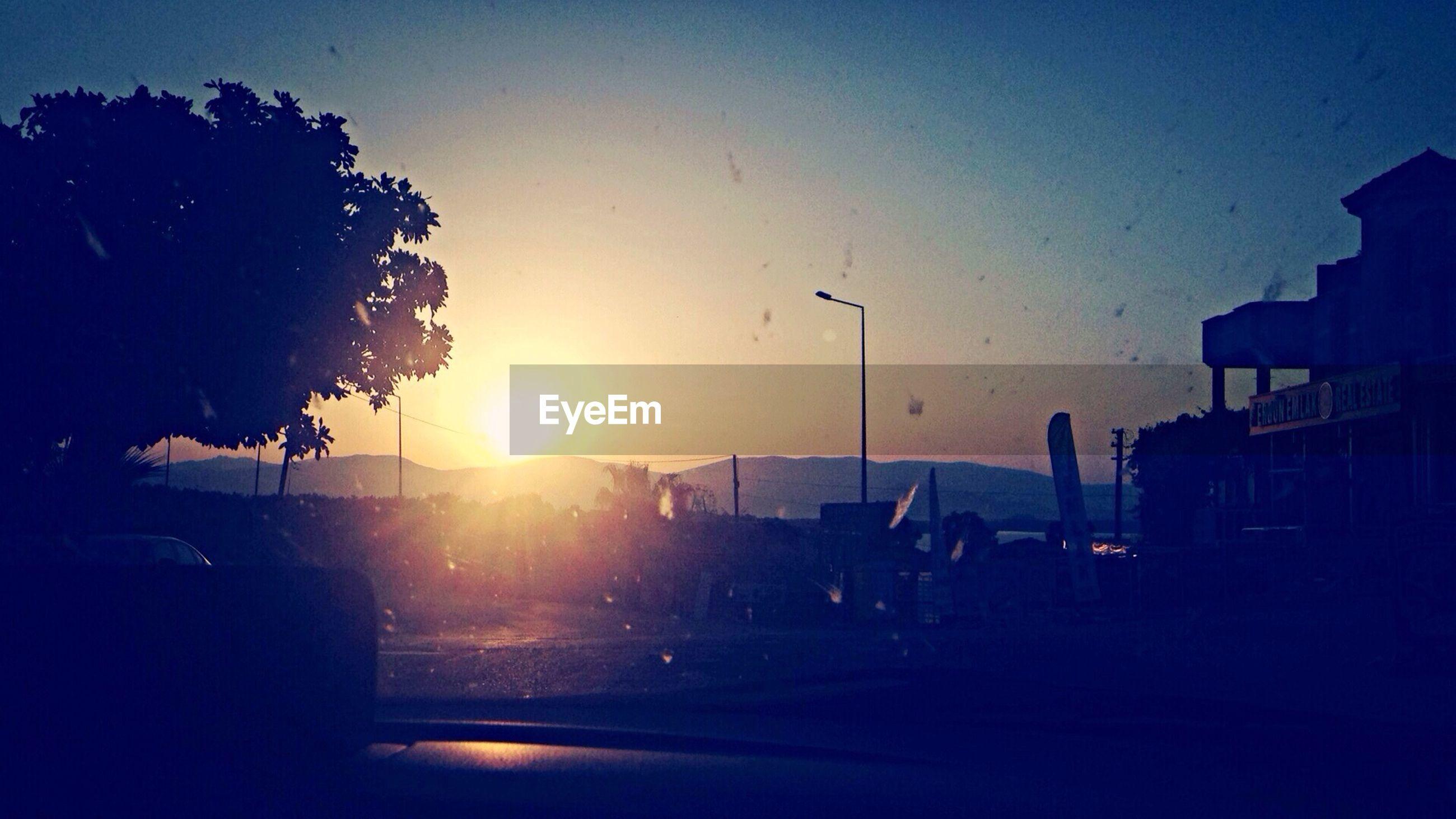 sunset, silhouette, sun, sky, sunlight, car, building exterior, sunbeam, built structure, lens flare, transportation, tree, dark, clear sky, architecture, street, land vehicle, nature, outdoors, road