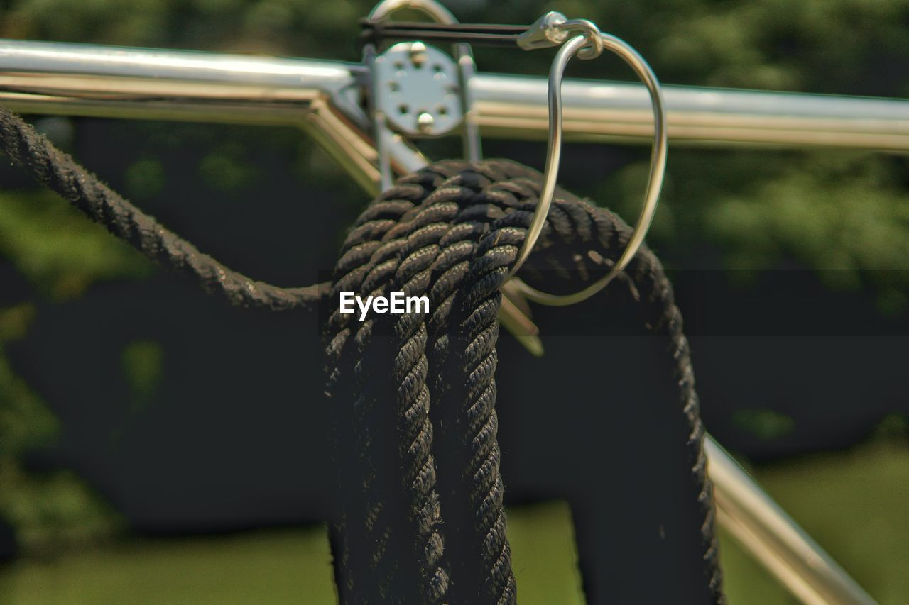 rope, strength, focus on foreground, metal, tied up, close-up, day, no people, connection, nature, outdoors, tied knot, playground, swing, equipment, cable, mode of transportation, detail, transportation, pattern, wheel, outdoor play equipment